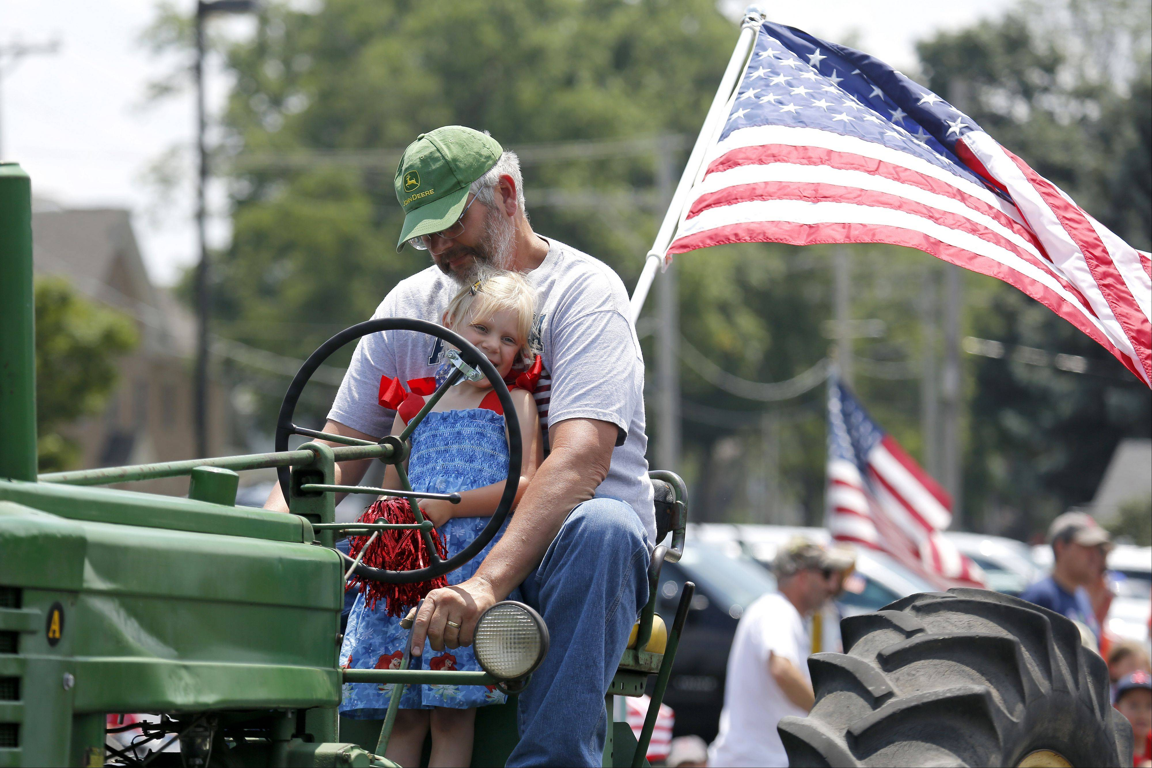 Five-year-old Bethany Volkening Helps her grandfather John Volkening out on his tractor during the Sugar Grove Fourth of July Parade Thursday. Both are from Sugar Grove.