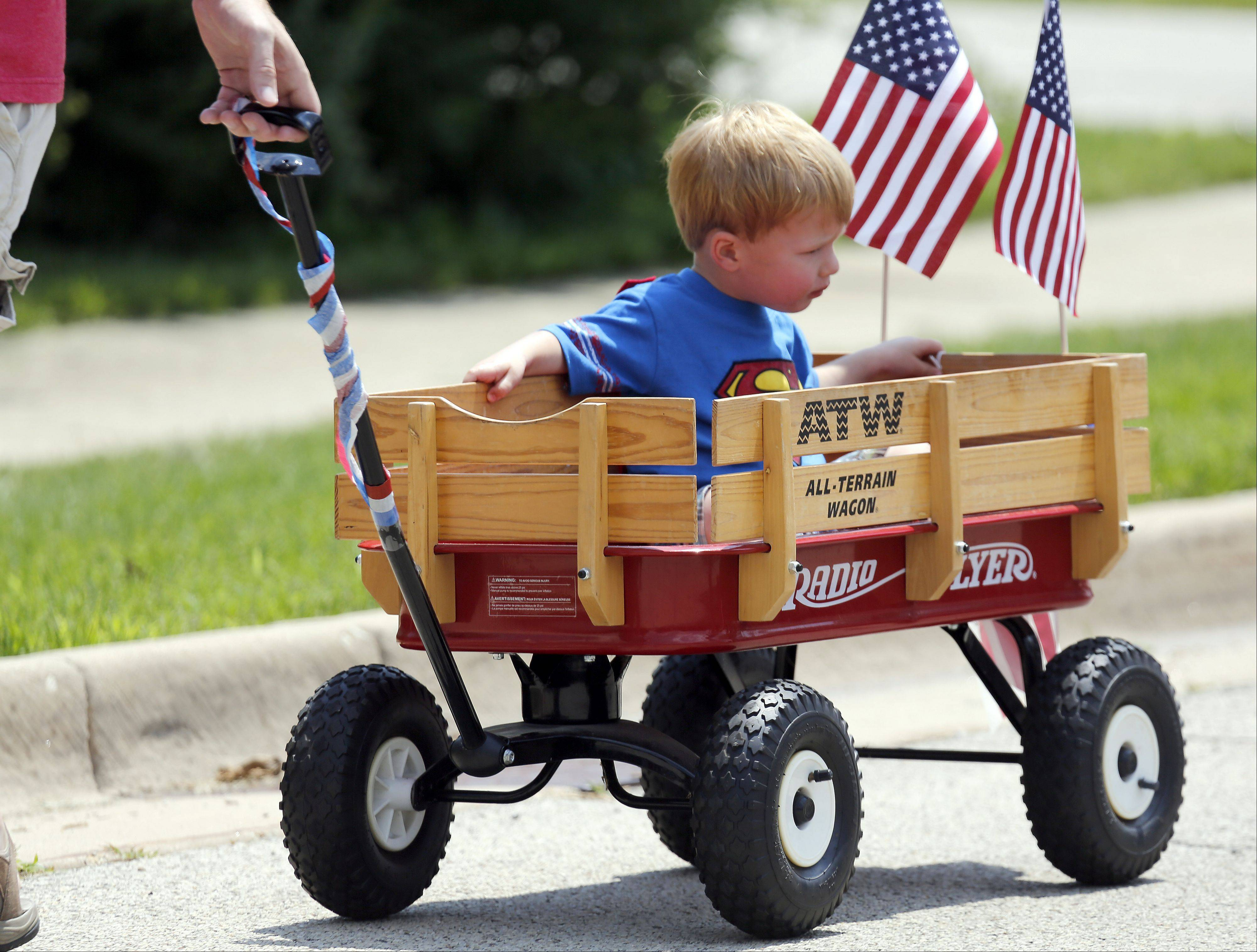 Two-year-old Logan Schroll of Sugar Grove keeps it rolling with a little help from his dad during the Sugar Grove Fourth of July Parade Thursday.