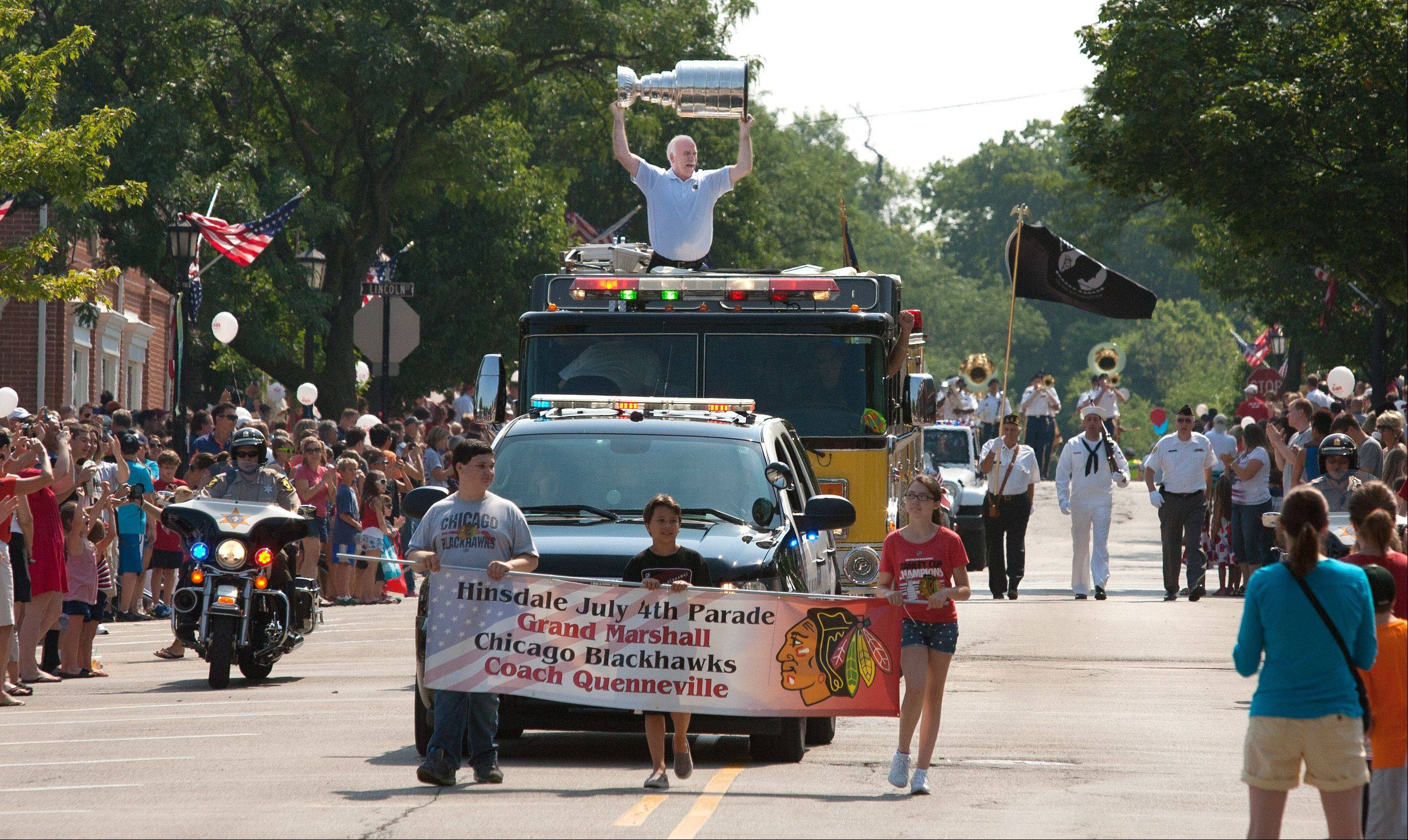 Chicago Blackhawk coach Joel Quenneville celebrates a Stanley Cup victory, as the grand marshall thrills his hometown Hinsdale July Fourth parade route.