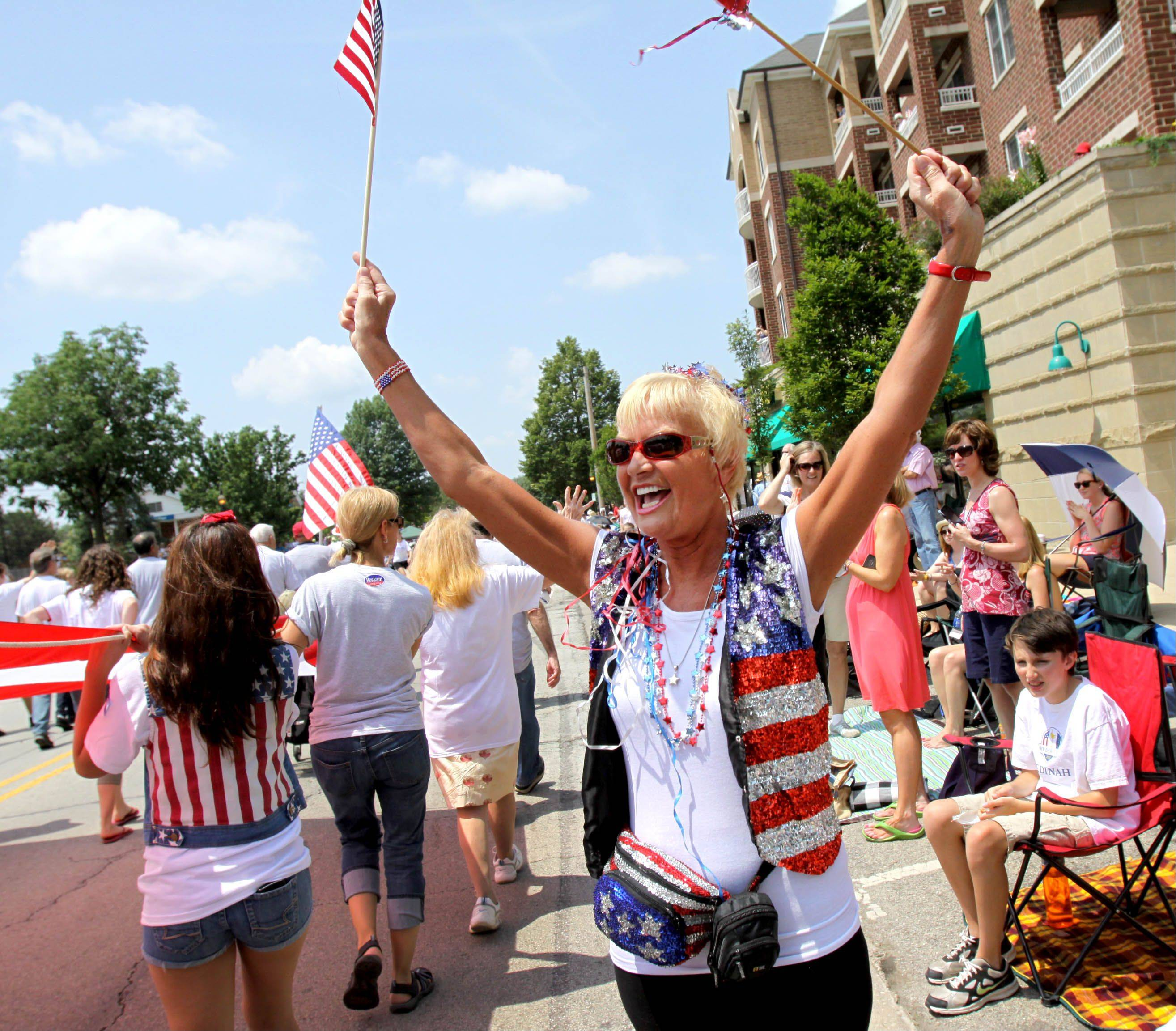 Diane Telander of Glen Ellyn cheers and waves as the 4th of July parade goes by on Crescent Boulevard in Glen Ellyn on Thursday.