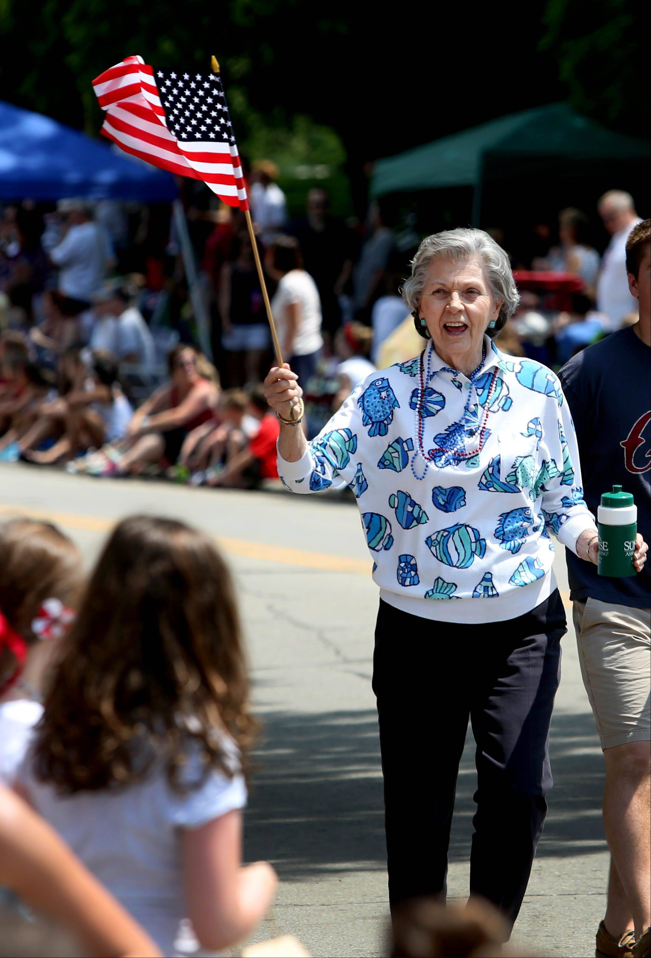 June Franks from Sunrise Senior Living center in Glen Ellyn, waves the flag and hands out water bottles as she takes part in the 4th of July parade in Glen Ellyn on Thursday.