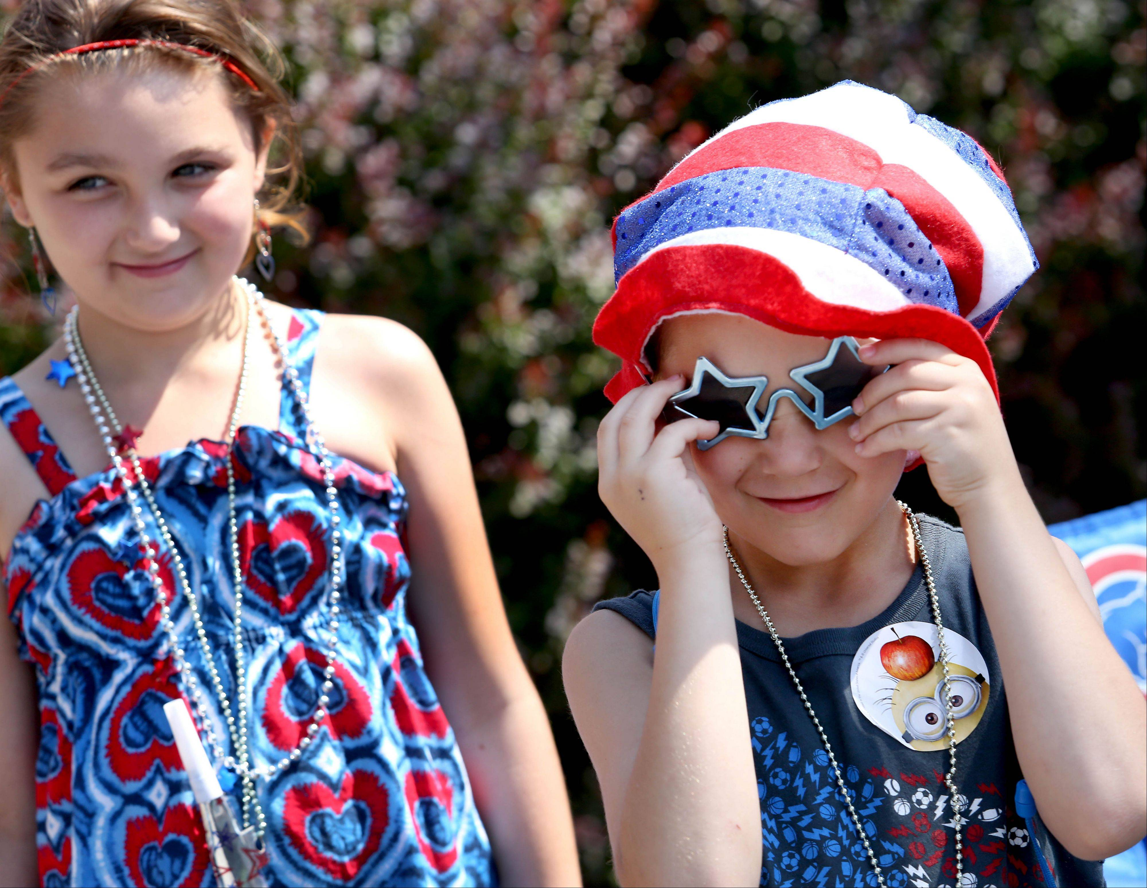 Margarette Spencer, 8, left and her brother Aidan, 6, of West Chicago, are decked out in red, white and blue as they wait for the 4th of July parade in Wheaton on Thursday.