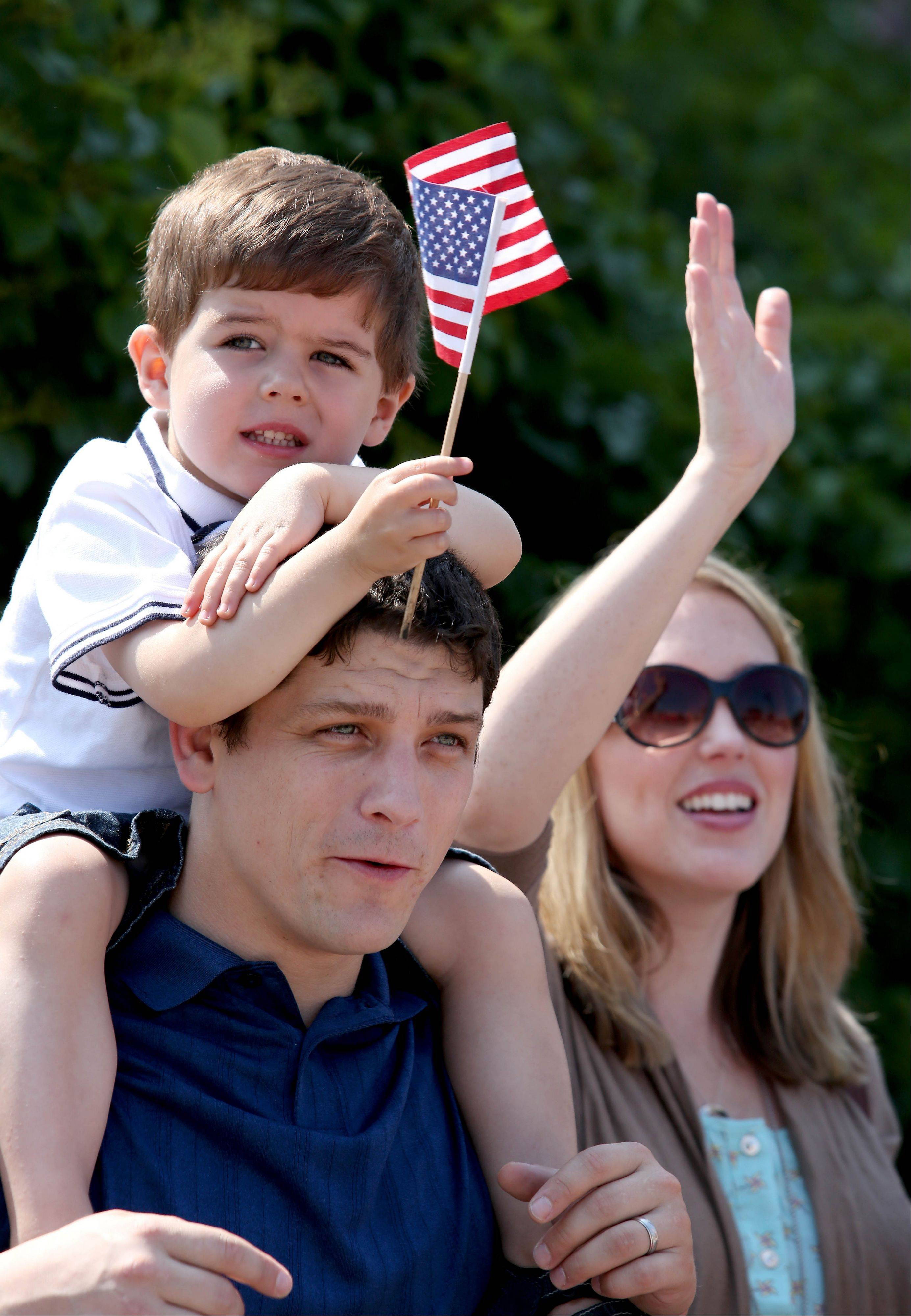 Tyler and Erin Birt of Wheaton with their son Ryan, 3, watch the 4th of July parade go by in Wheaton on Thursday.