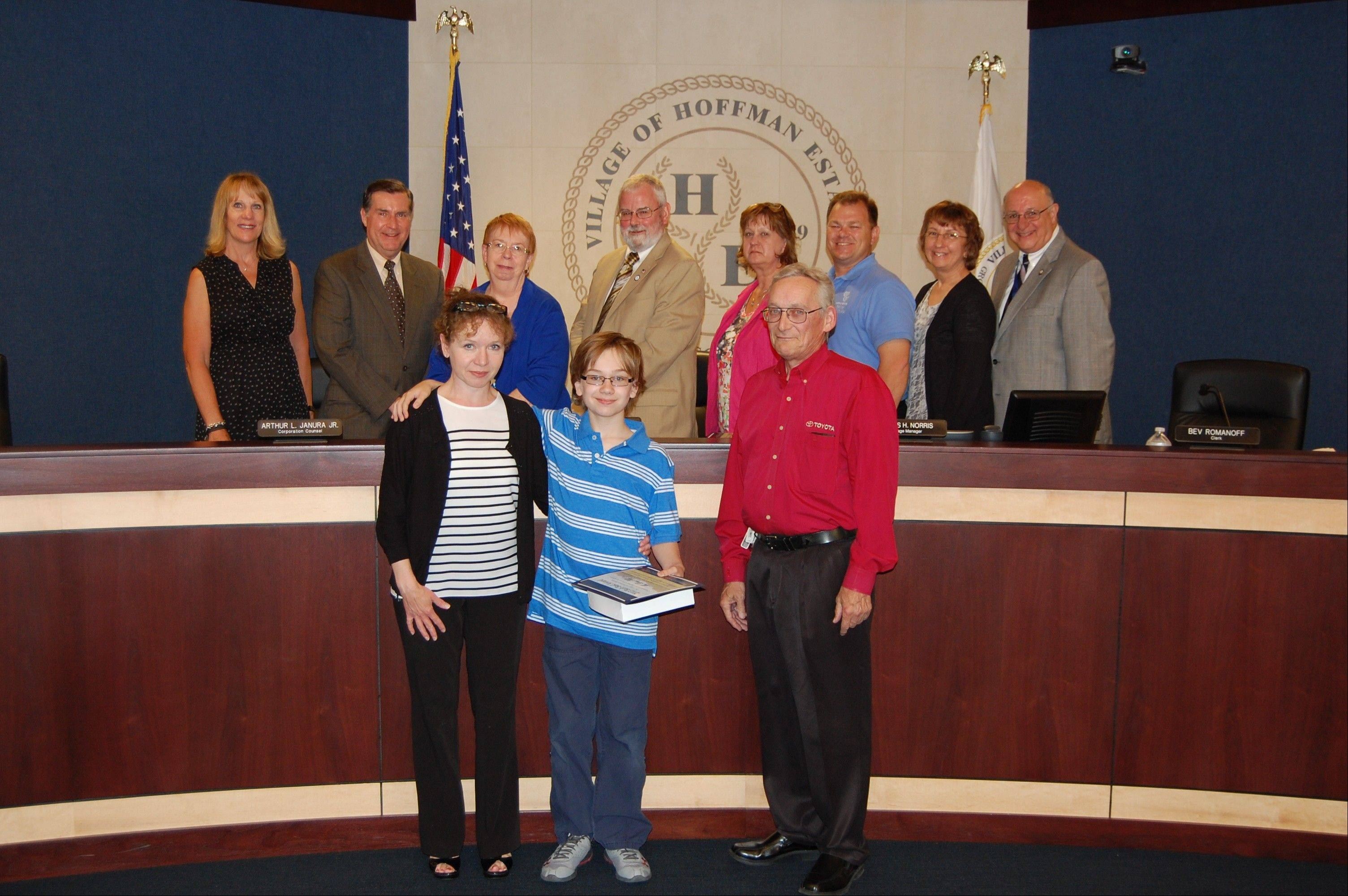 Doug Hill, center, a 2013 recipient of the Barb Basl Award, pictured with the Hoffman Estates village board and his family.