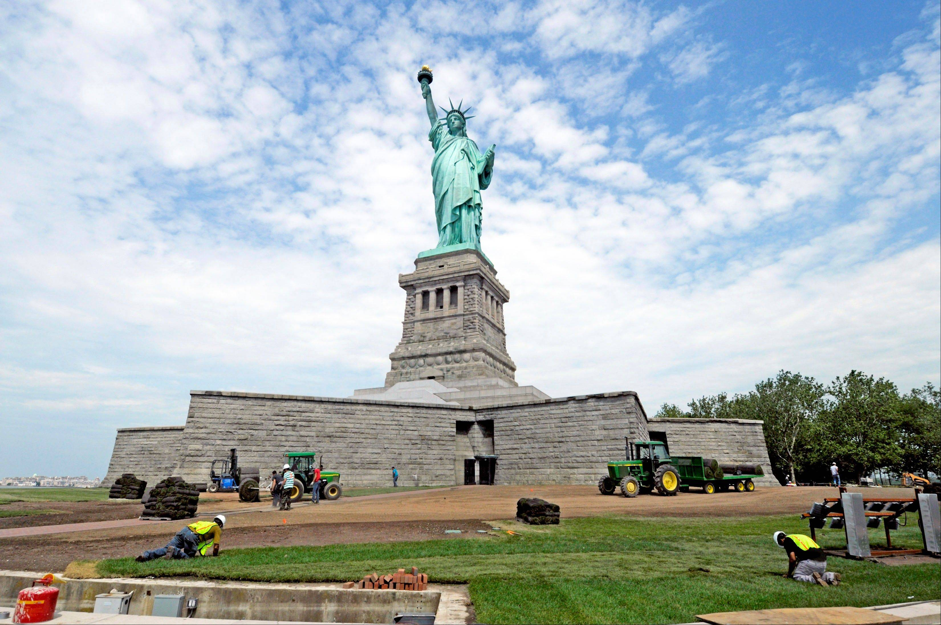 In this June 26, 2013 photo provided by the National Park Service, workers on Liberty Island install sod around the national monument which is set to re-open on the 4th of July, in New York. Months after railings broke, docks and paving stones were torn up and buildings were flooded by Superstorm Sandy, the Statue of Liberty will finally welcome visitors again.