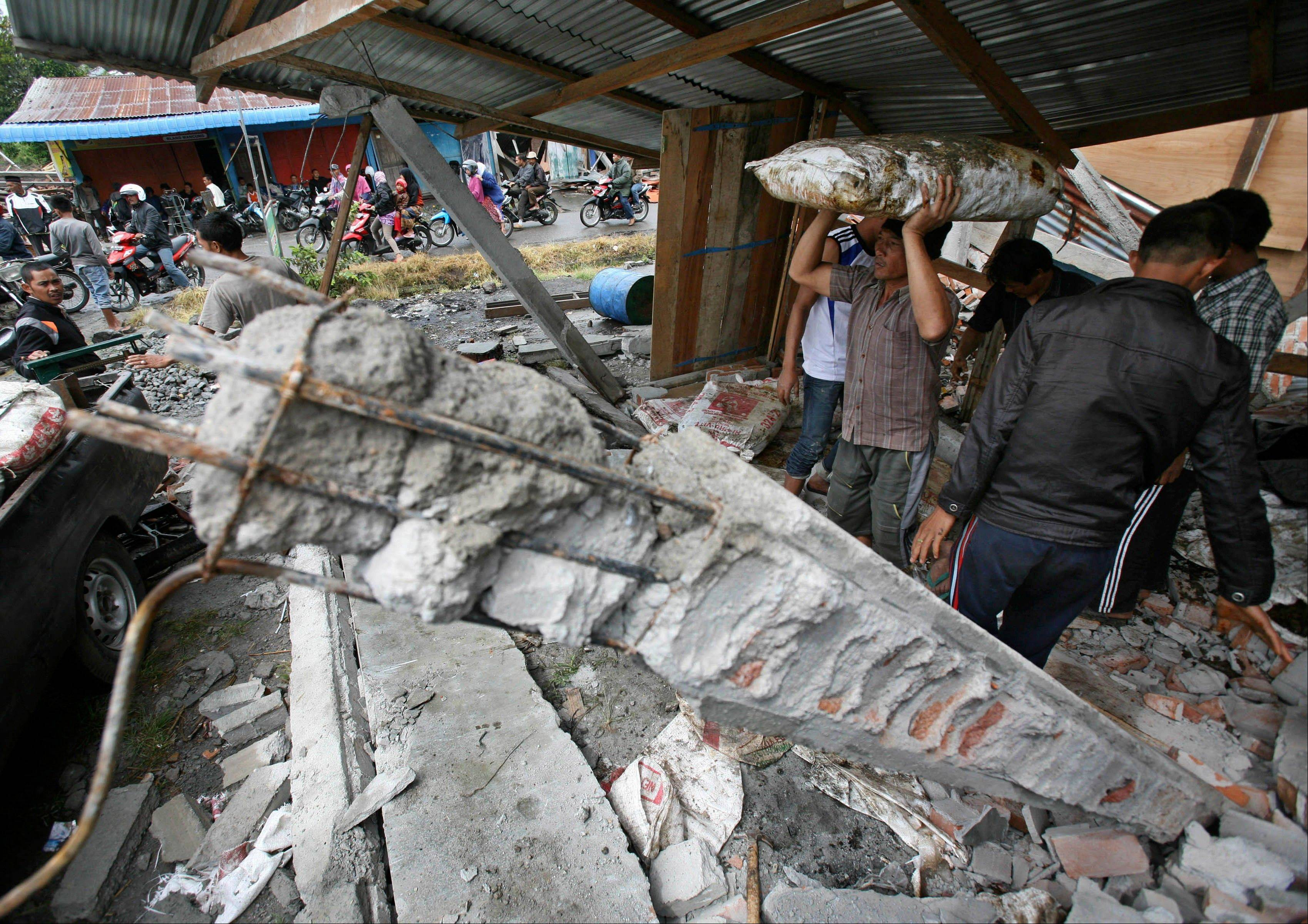 An Acehnese man carries a sack of rice he salvaged from a shop destroyed by Tuesday's earthquake at a market in Blang Mancung, Aceh province, Indonesia, Thursday, July 4, 2013. The death toll from an earthquake that hit Indonesia's Aceh province earlier this week has reached 30, and police and soldiers are searching the debris for another 12 people believed missing, officials said Thursday.