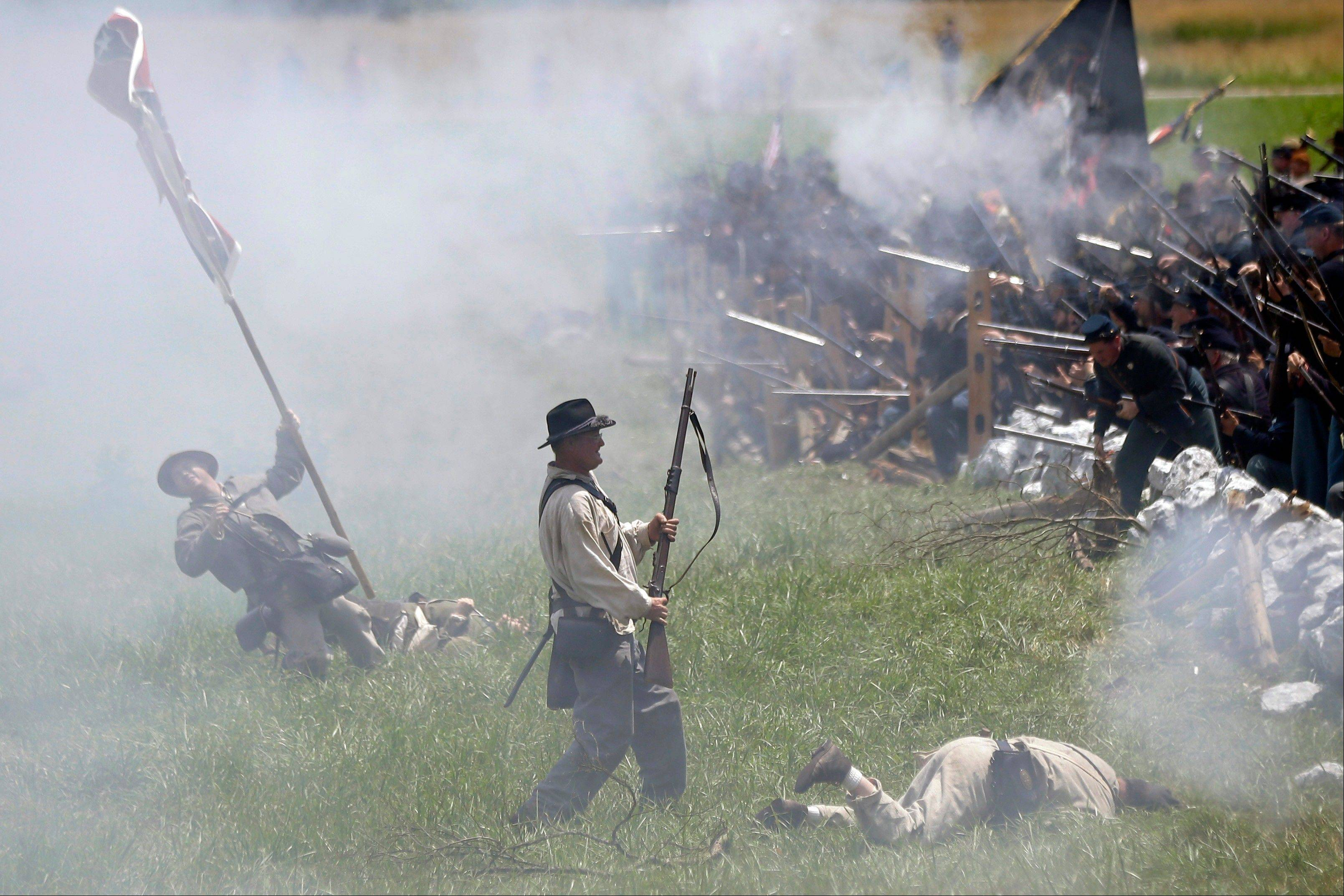 "In this June 30, 2013 file photo, re-enactors portray Pickett's Charge during ongoing activities commemorating the 150th anniversary of the Battle of Gettysburg at Bushey Farm in Gettysburg, Pa. One of the most difficult challenges for any mock general at a Civil War battle re-enactment is deciding which of his men must ""die."""