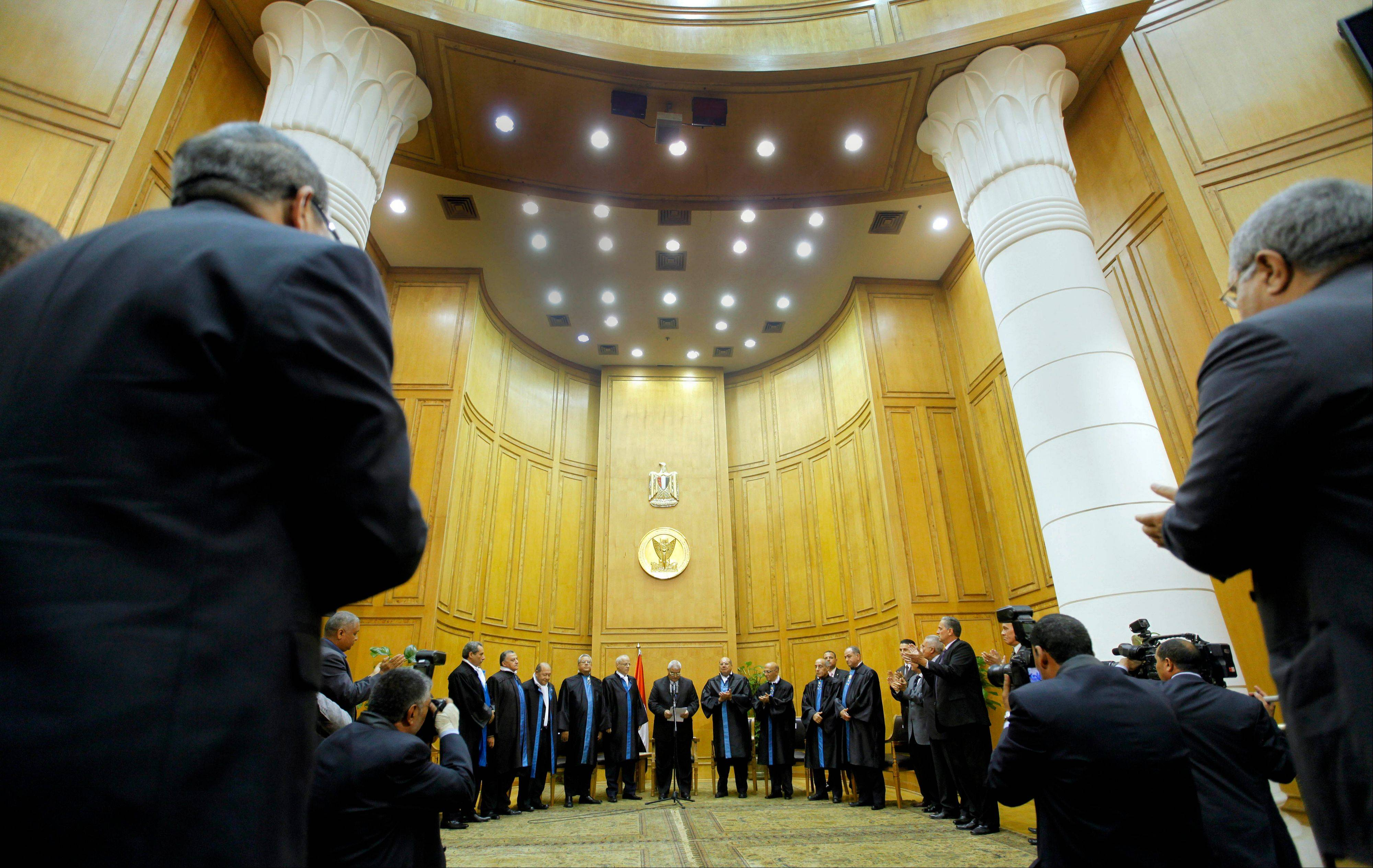 Egypt's chief justice Adly Mansour, center, is applauded at his swearing in ceremony as the nation's interim president Thursday, July 4, 2013. The chief justice of Egypt's Supreme Constitutional Court was sworn in Thursday as the nation's interim president, taking over hours after the military ousted the Islamist President Mohammed Morsi.