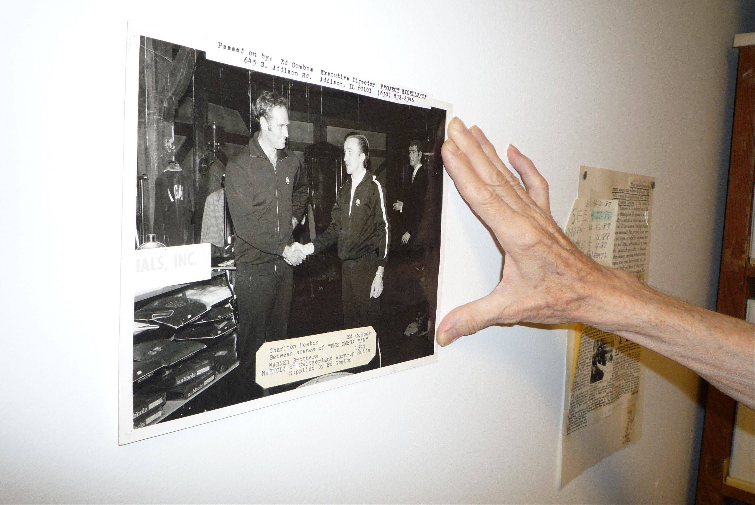 "Using the same hand that once shook the hand of Charlton Heston, Ed Gombos holds this 1970 photograph of their handshake while on the movie set of ""The Omega Man."" Gombos, of Addison, supplied the warm-up suit Heston wore in the movie, and the pair remained in touch until Heston's death in 2008."
