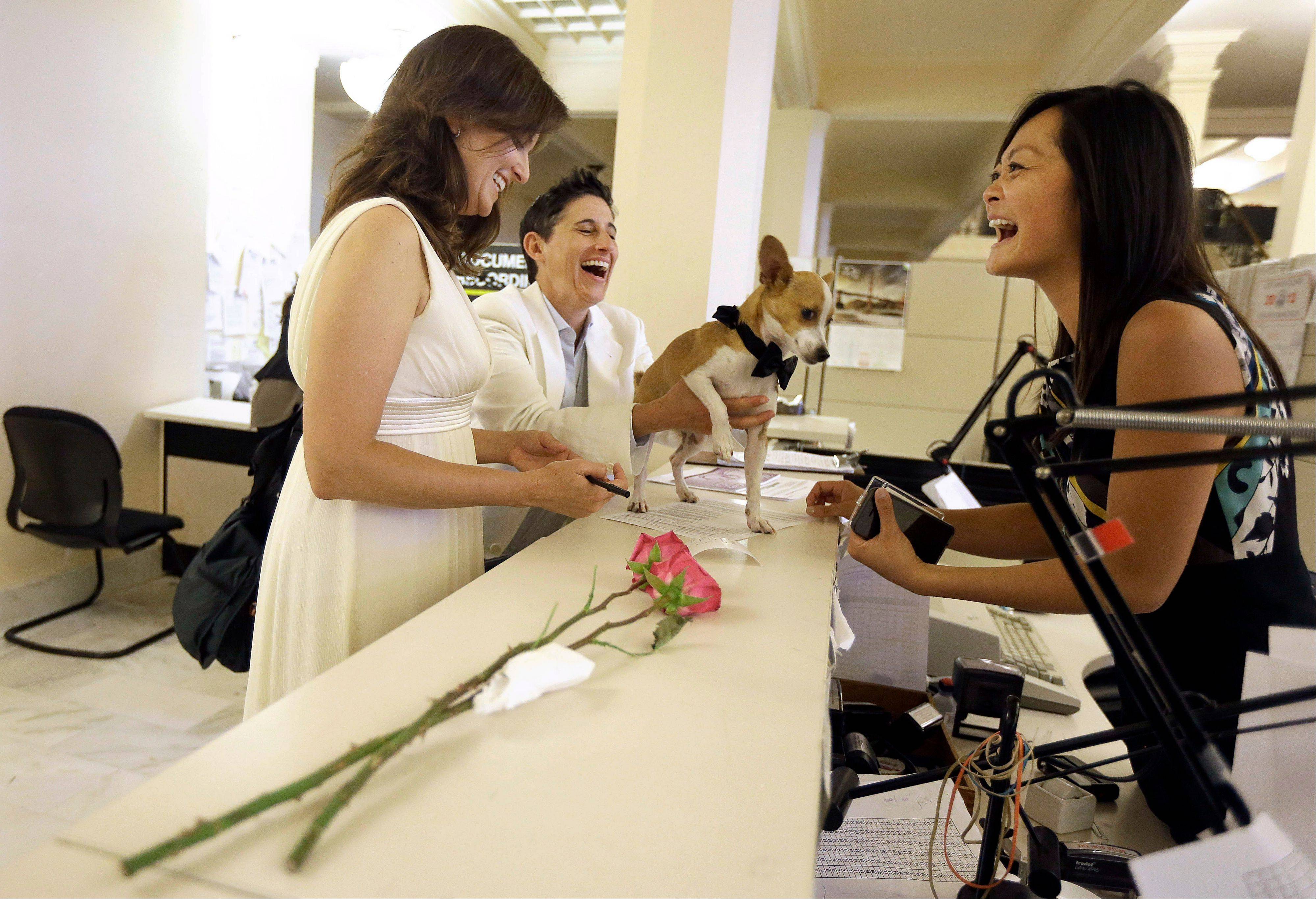 "Assessor-Recorder Carmen Chu, right, laughs as Jen, left, and Frances Rainin's dog Punum climbs on the counter as they fill out paper work for their marriage certificate after they were married at City Hall in San Francisco, Friday, June 28, 2013. A three-judge panel of the 9th U.S. Circuit Court of Appeals issued a brief order Friday afternoon dissolving, ""effective immediately,"" a stay it imposed on gay marriages while the lawsuit challenging the ban advanced through the courts."