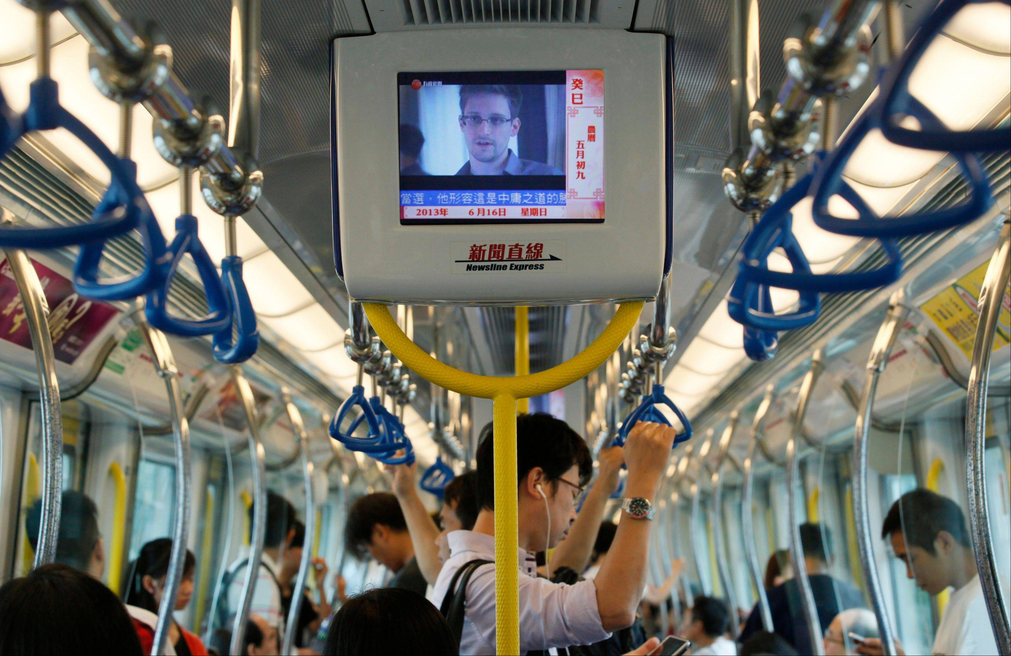 In this June 16, 2013 file photo a television screen shjows the news of Edward Snowden, a former CIA employee who leaked top-secret documents about sweeping U.S. surveillance programs, in the underground train in Hong Kong.