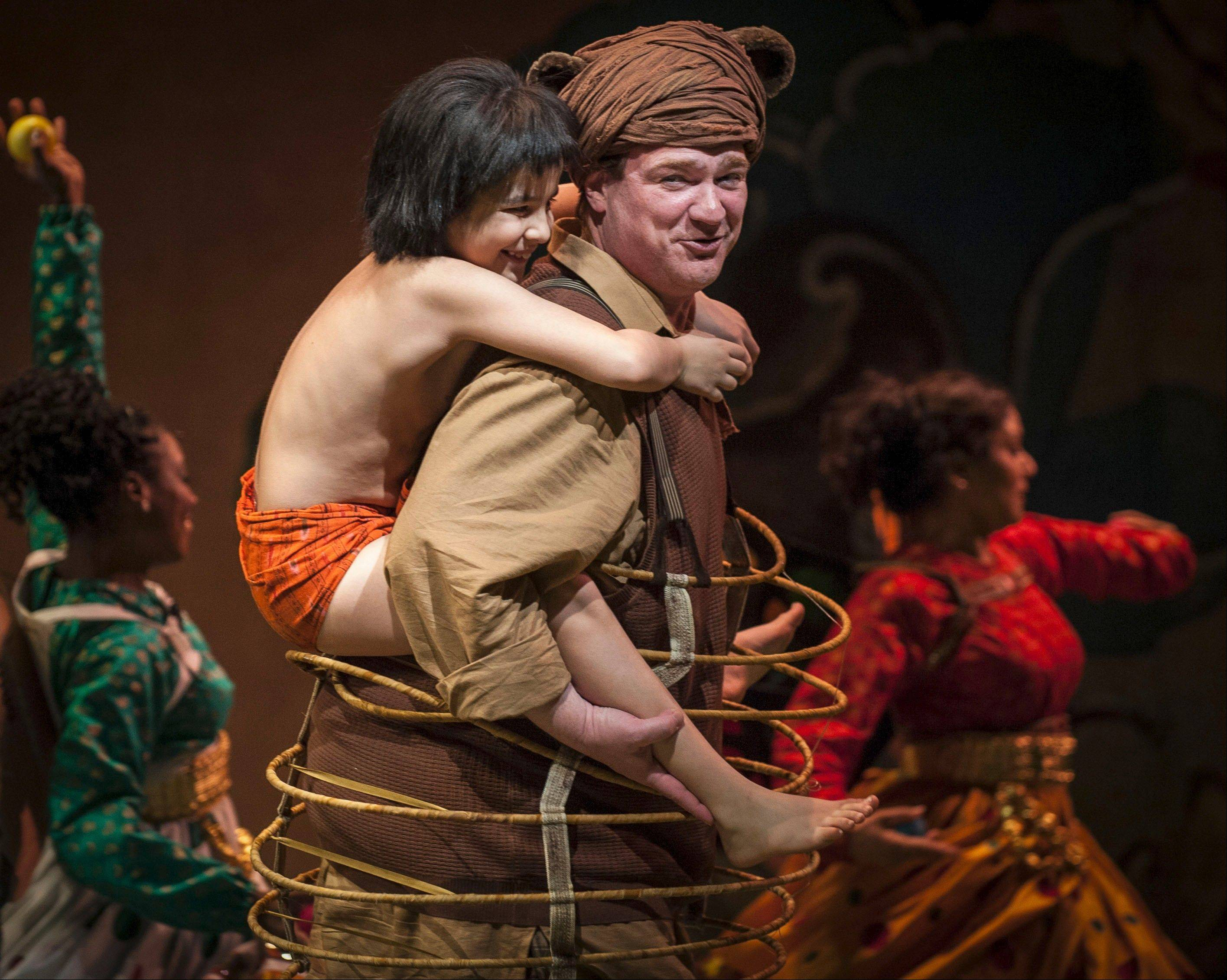 "Young Mowgli (Akash Chopra), left, finds a friend in the easygoing Baloo in Goodman Theatre's ""The Jungle Book,"" adapted and directed by Mary Zimmerman."