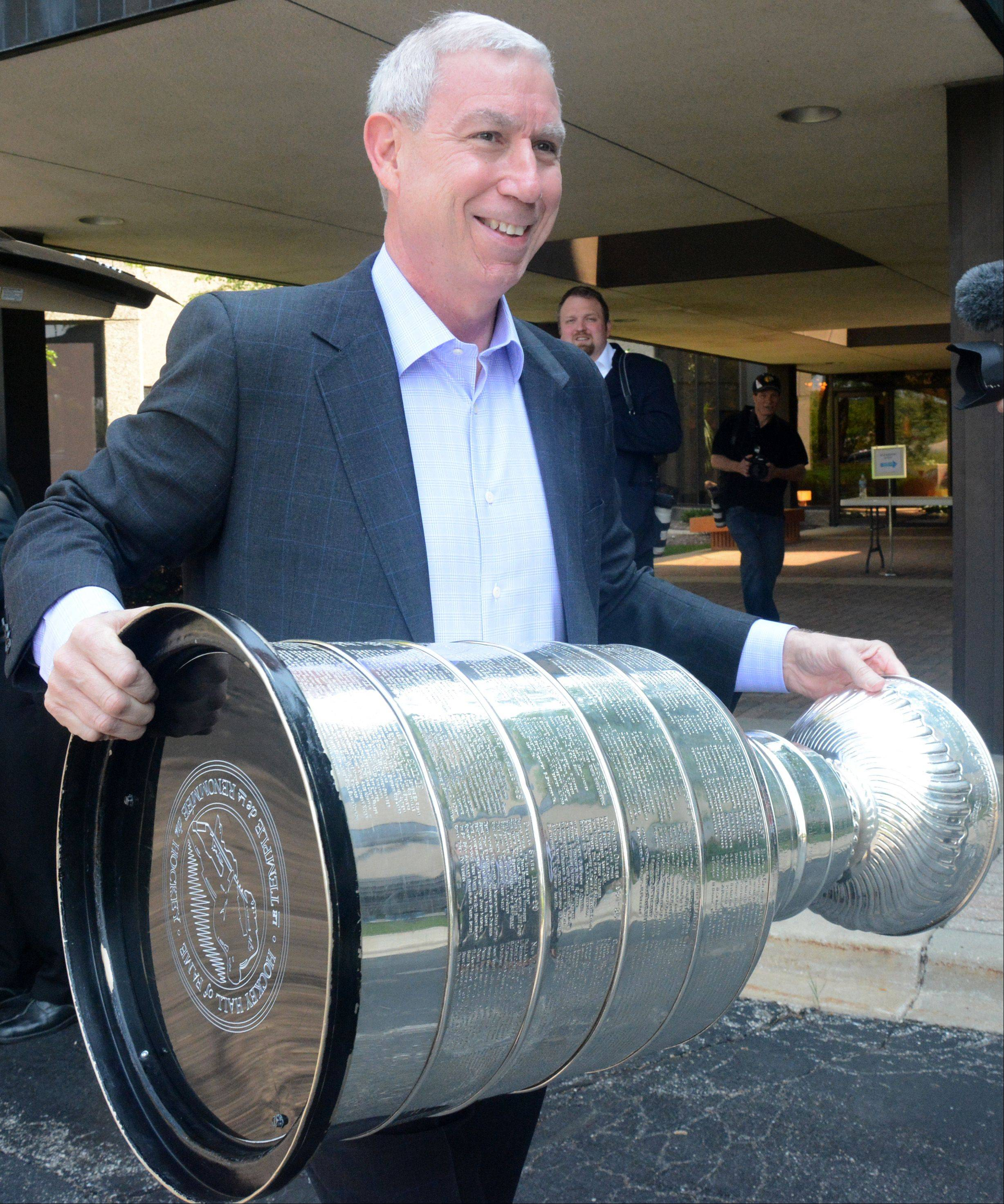 Hawks President John McDonough carries the Stanley Cup into the Daily Herald office Friday in Arlington Heights.