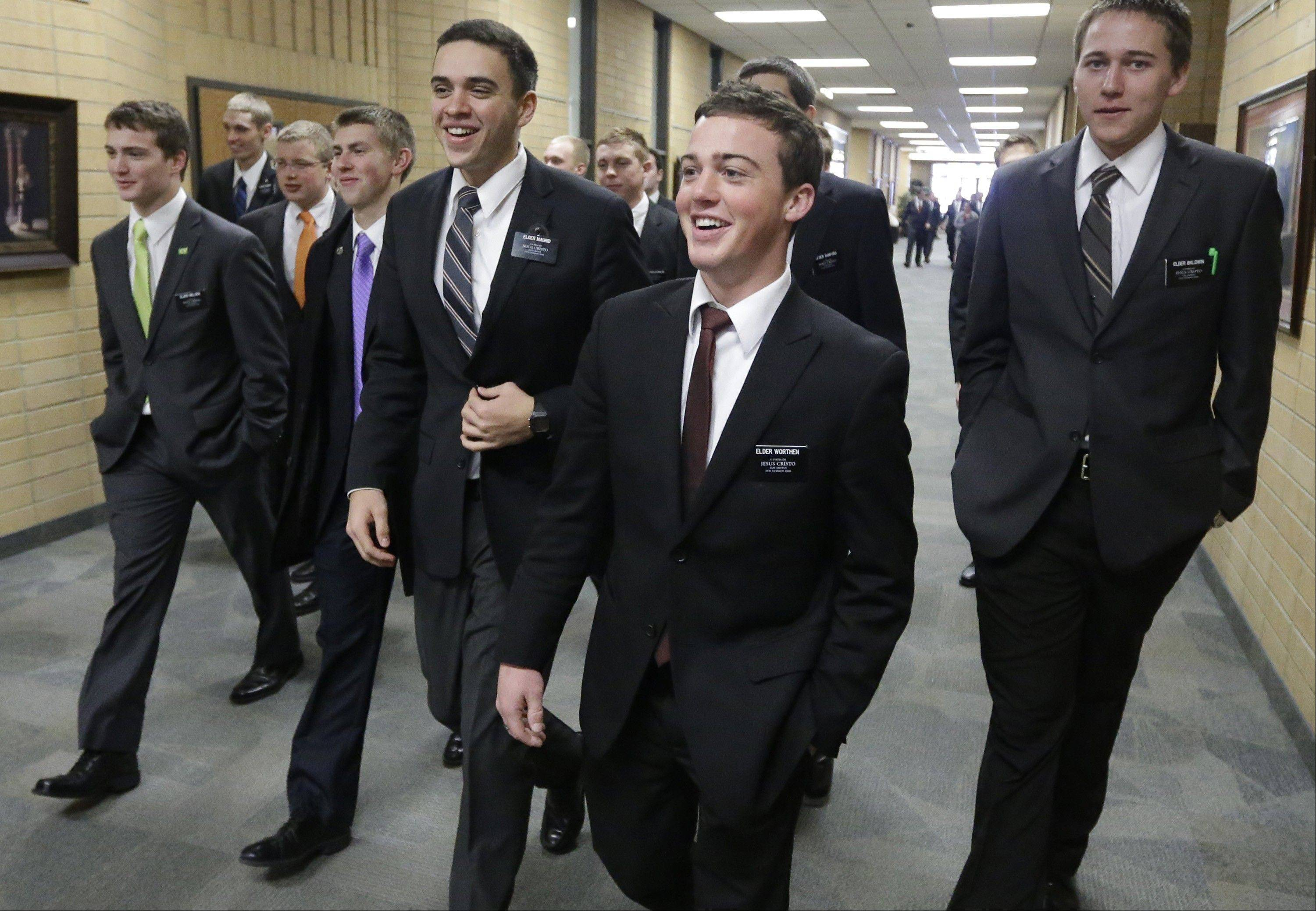 Mormon missionaries walk through the halls at the Missionary Training Center in Provo, Utah. The Mormon church is preparing to blanket the globe with more missionaries than ever as a surge of young men and women pack their white shirts, ties and knee-length skirts.