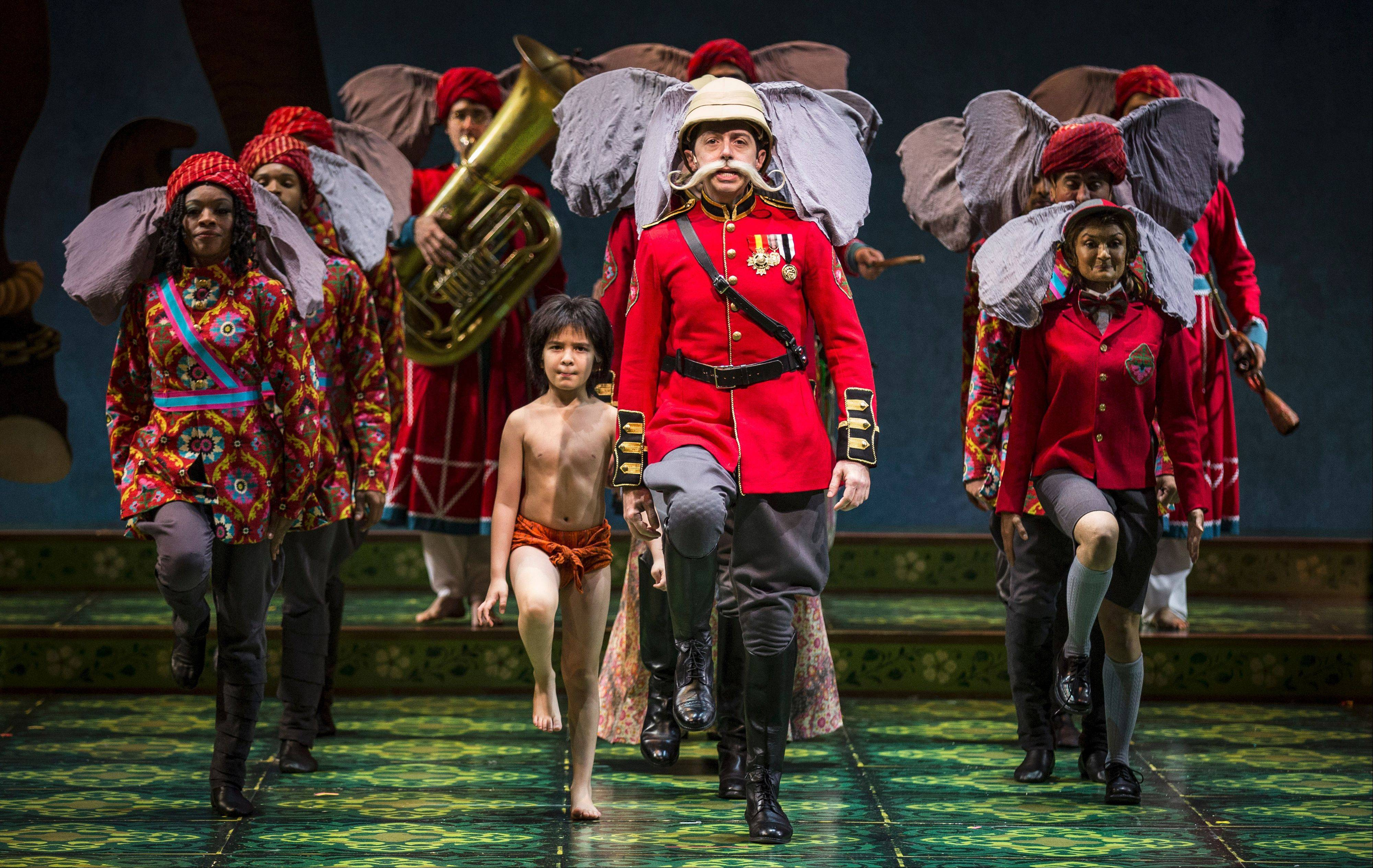 "The elephant brigade -- under the command of the slightly dotty Colonel Hathi (Ed Kross), center -- gets some assistance from the man-cub Mowgli (Akash Chopra) in Goodman Theatre's world premiere of ""The Jungle Book."""