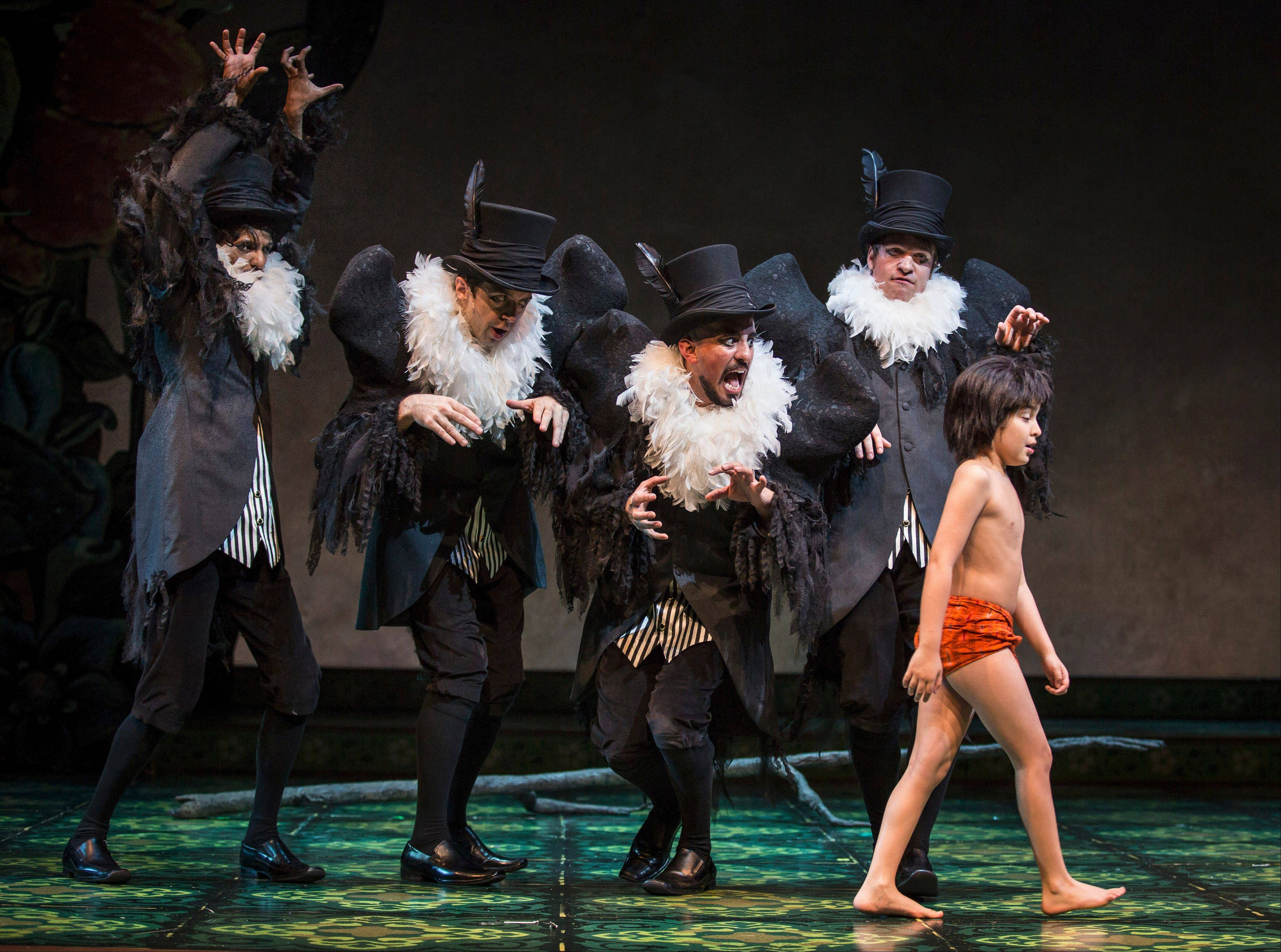 "Vultures try to lure young Mowgli (Akash Chopra), who has run away from the pals who want to return him to his village, in Goodman Theatre's ""The Jungle Book,"" inspired by Rudyard Kipling's stories and the 1967 Disney film."