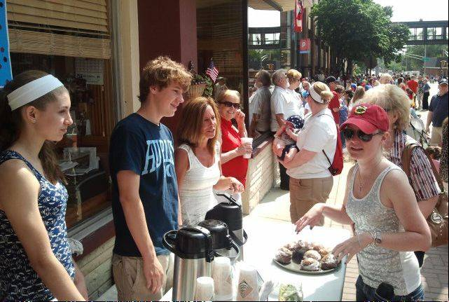 Russell Lissau/rlissau@dailyherald.com At left, Kaela Drum, Logan Boven, and Vicki Boven chat with parade goers as they sell drinks and muffins outside the Uptown Cafe in Arlington Heights at the start of the Independence Day parade.