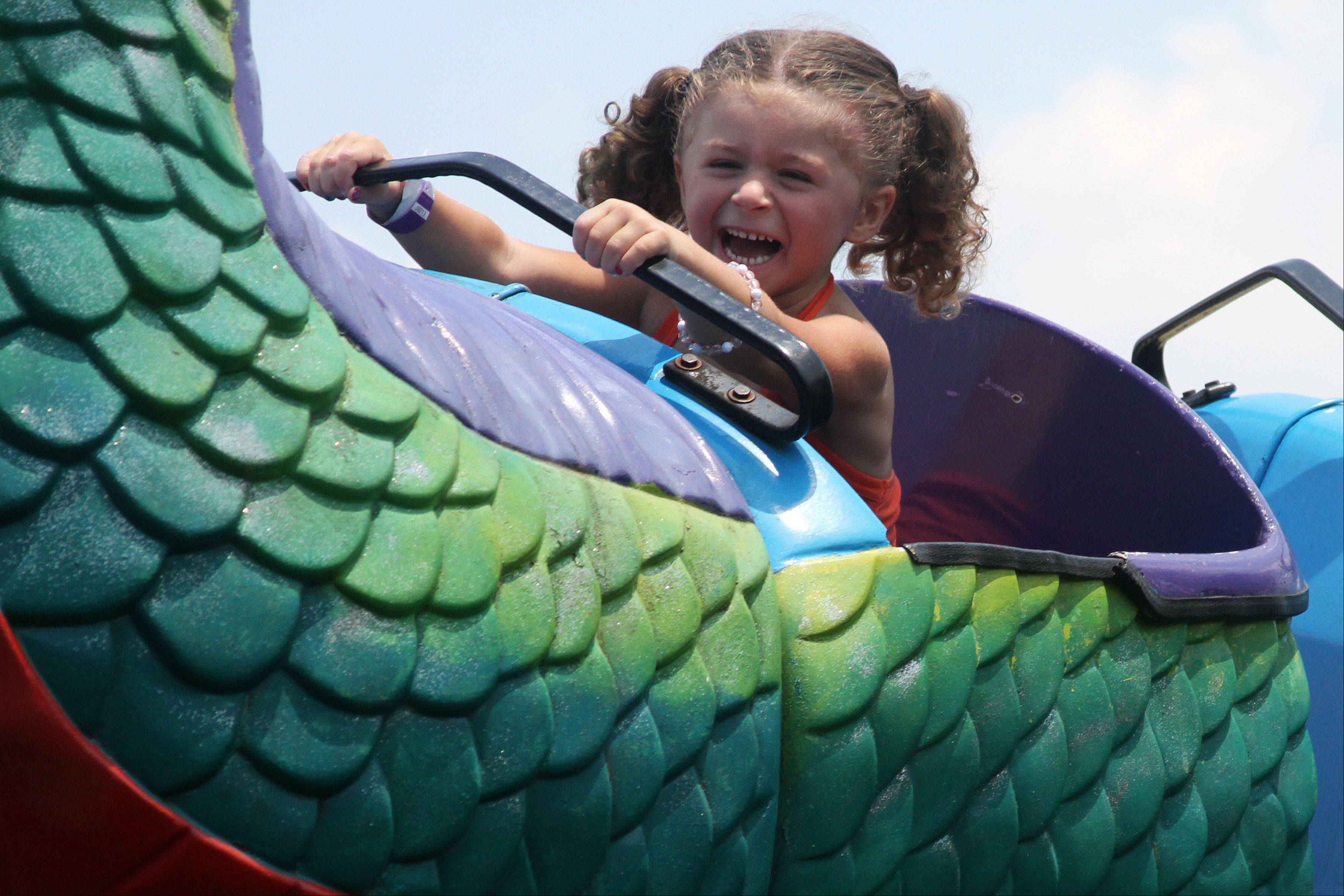 Madilyn Svejda, 4, of Plainfield rides the dragon roller coaster at the Naperville Exchange Club's 26th annual Ribfest on Friday.