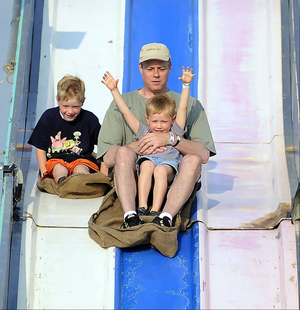 Dan VandeVelde and his sons Eric,4, and Alex,6, formerly of Hoffman Estates, hit the giant slide at the Northwest Fourth-Fest in Hoffman Estates on Friday.
