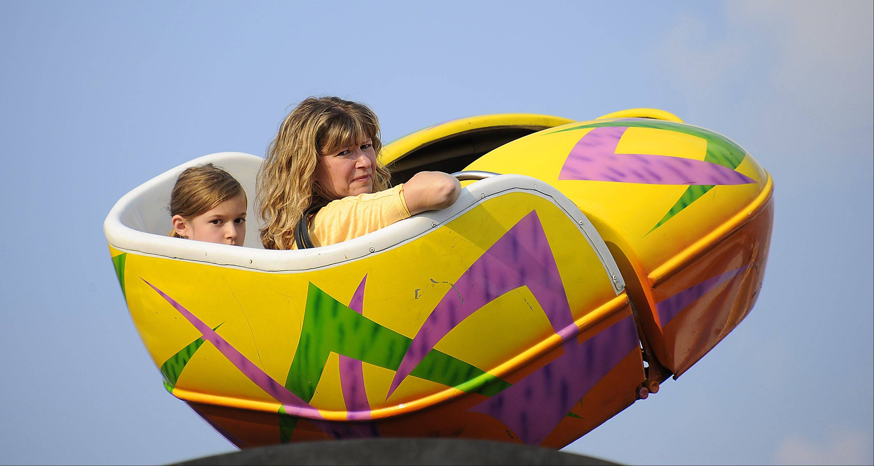 Wendy Maslankowski and her daughter Kylie,9, of Pingree Grove prepare to take a spin at the Northwest Fourth-Fest in Hoffman Estates on Friday.