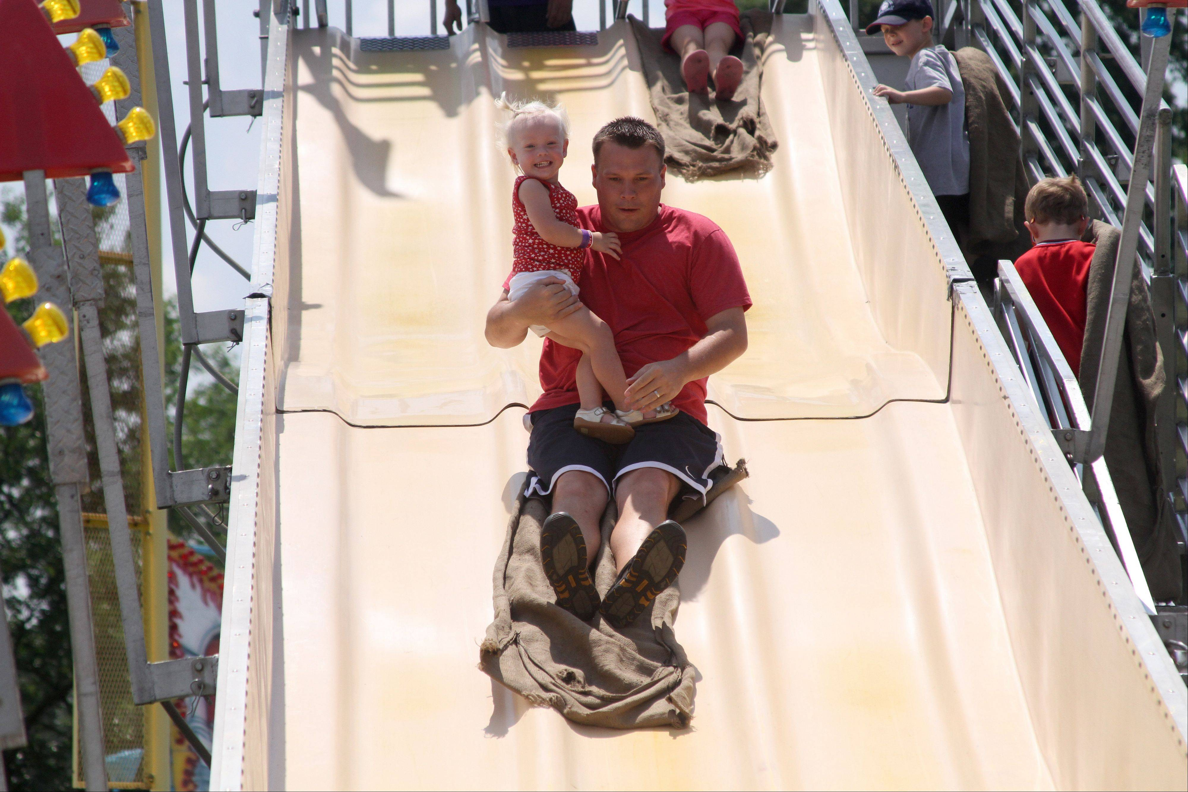 Brian Clark of Naperville holds his 2-year-old daughter Kailyn as they go down the Fun Slide at the Naperville Exchange Club's 26th annual Ribfest on Friday.
