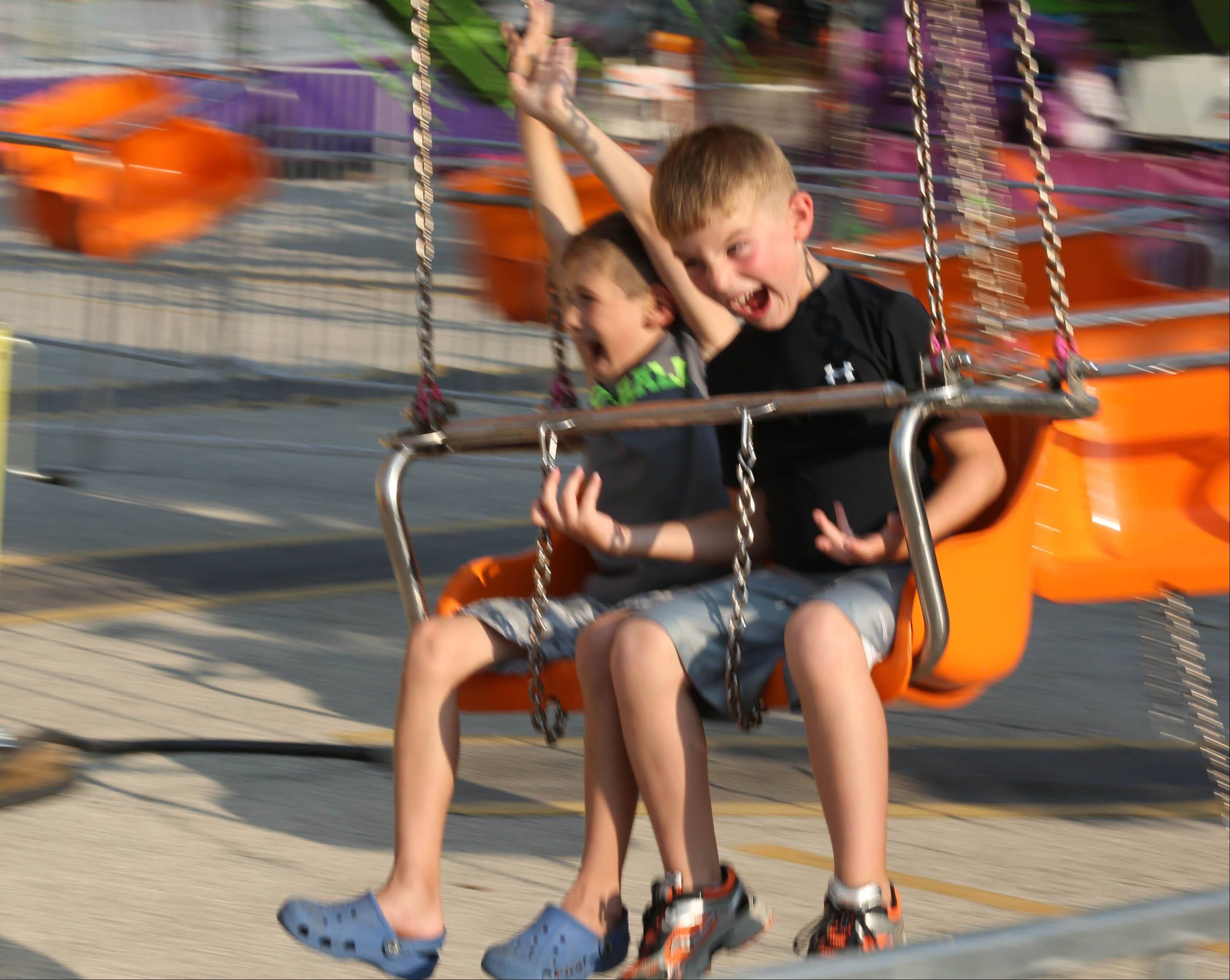 Michael Cruz,6, of Volo and Matthew Kisselburg,8, of Mundelein ride the swing at Mundelein Community Days at Kracklauer Park in Mundelein on Friday.