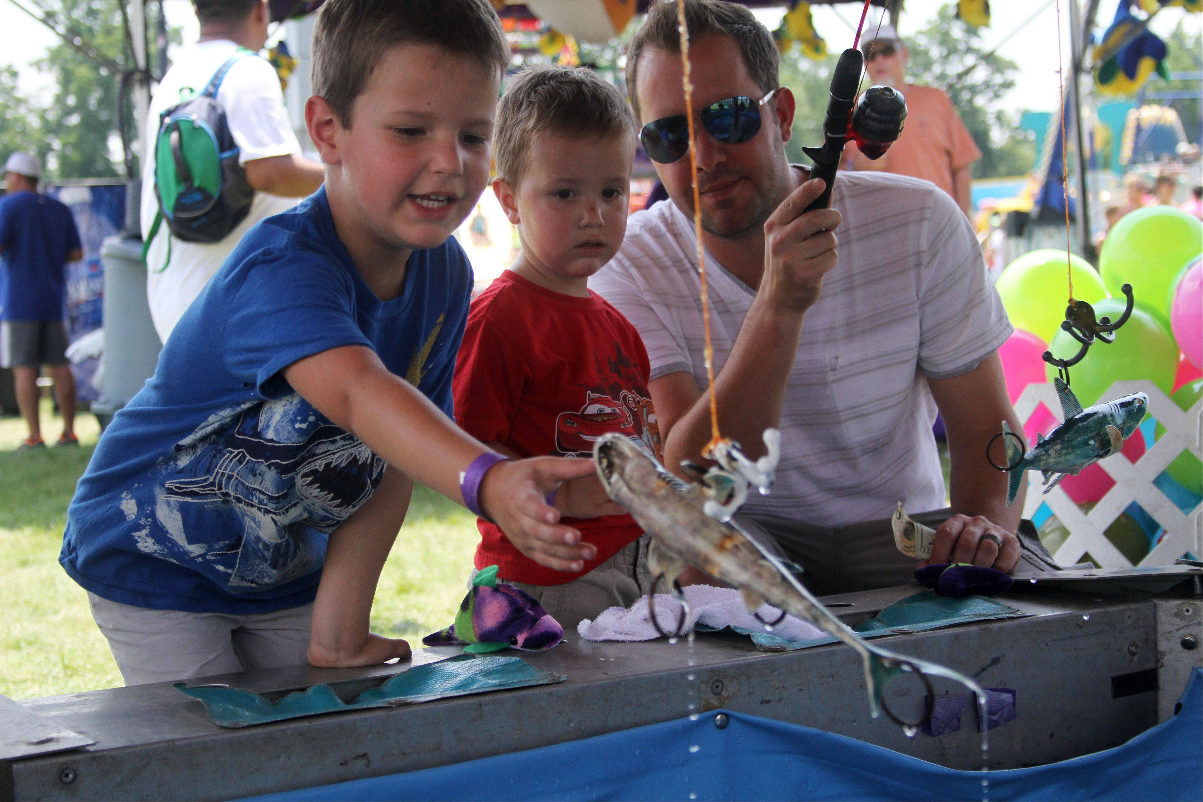 Blake Sweda, 5, left, claims the shark his mother helped him catch at the fishing game while his younger brother Tyler, 3,center, and father, Marc, watch him at the Naperville Exchange Club's 26th annual Ribfest .