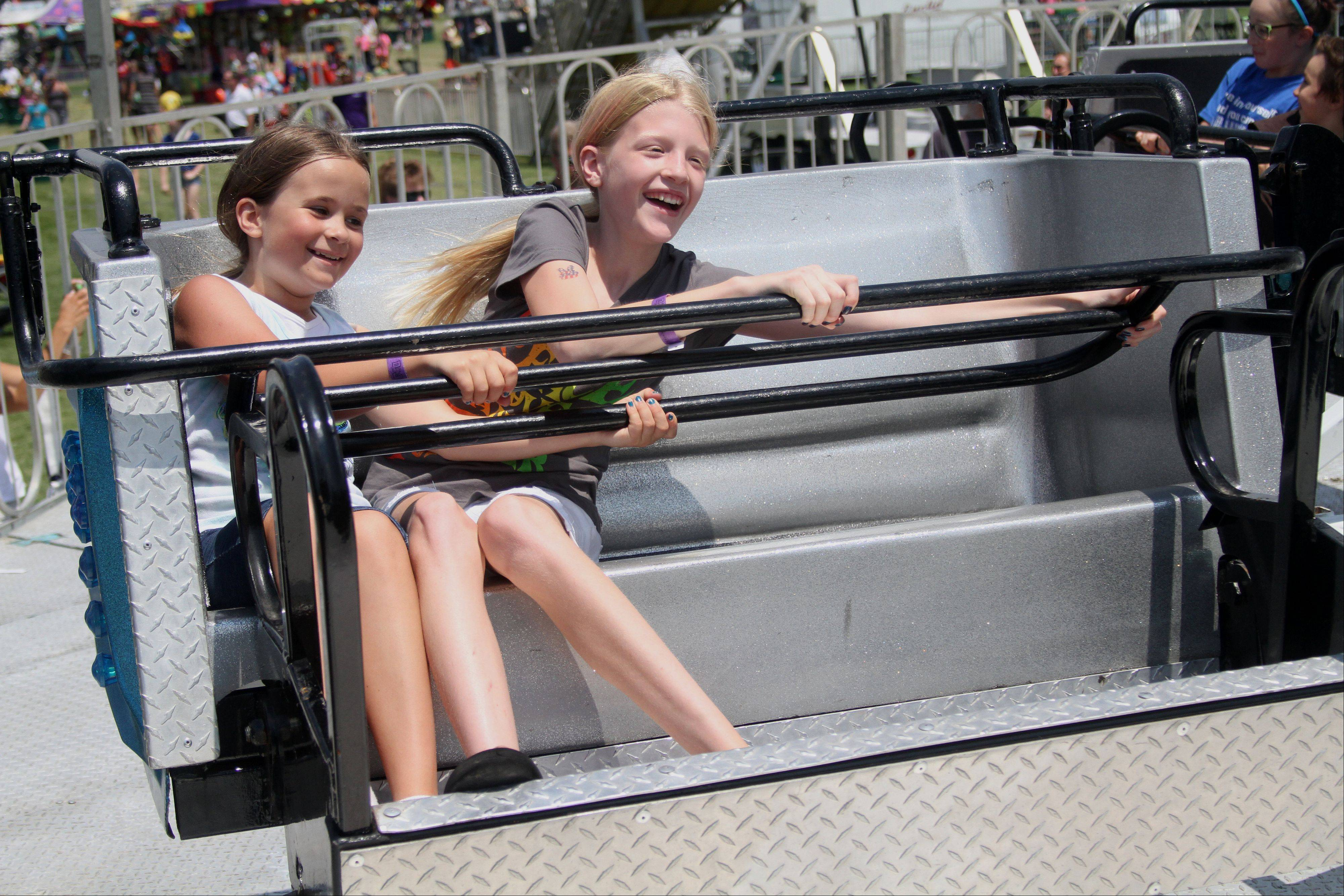 Molly Bergeron, 9, of Naperville, left, and Clare O'Donnell, 11, of Naperville ride the Sizzler ride at the Naperville Exchange Club's 26th annual Ribfest.