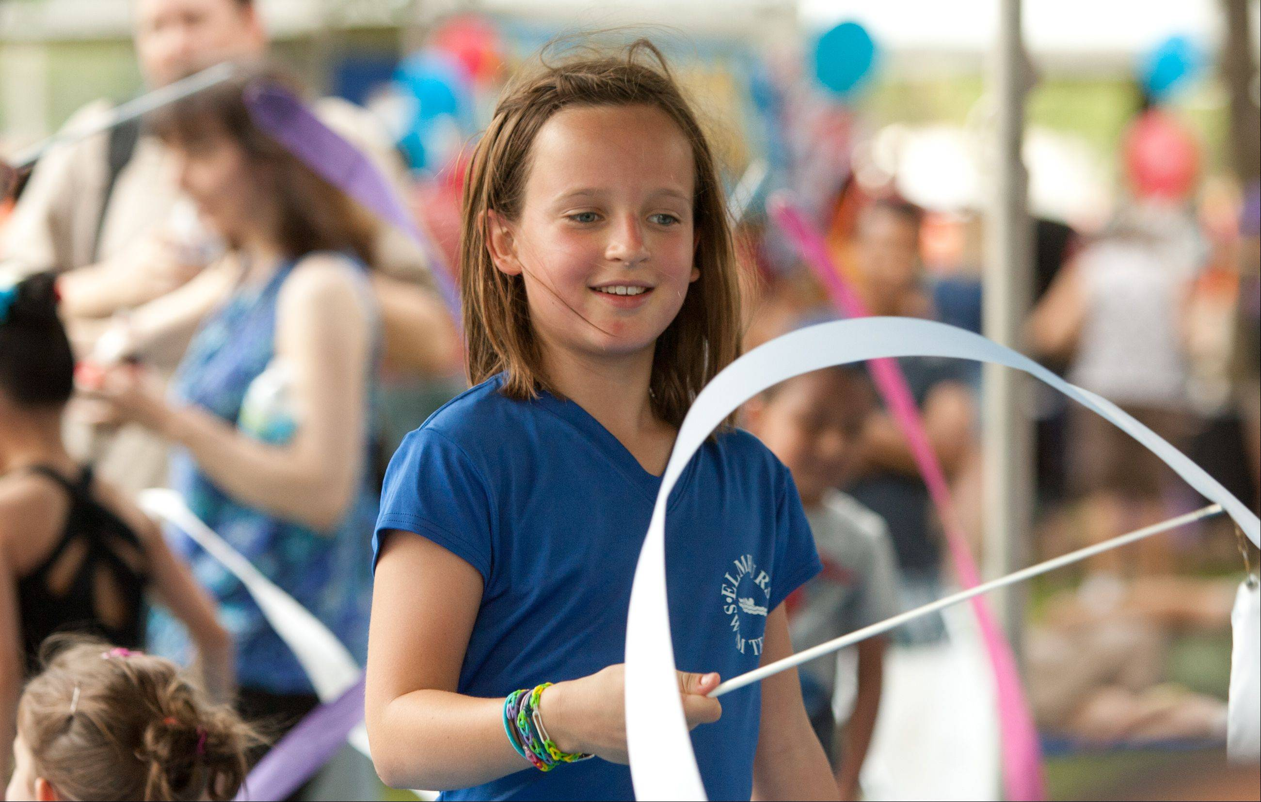 Julia Kevin, 10, of Elmhurst practices rhythmic exercises in the Elite Sports Complex of Downers Grove's booth, at the Eyes to the Skies Festival at Community Park in Lisle.