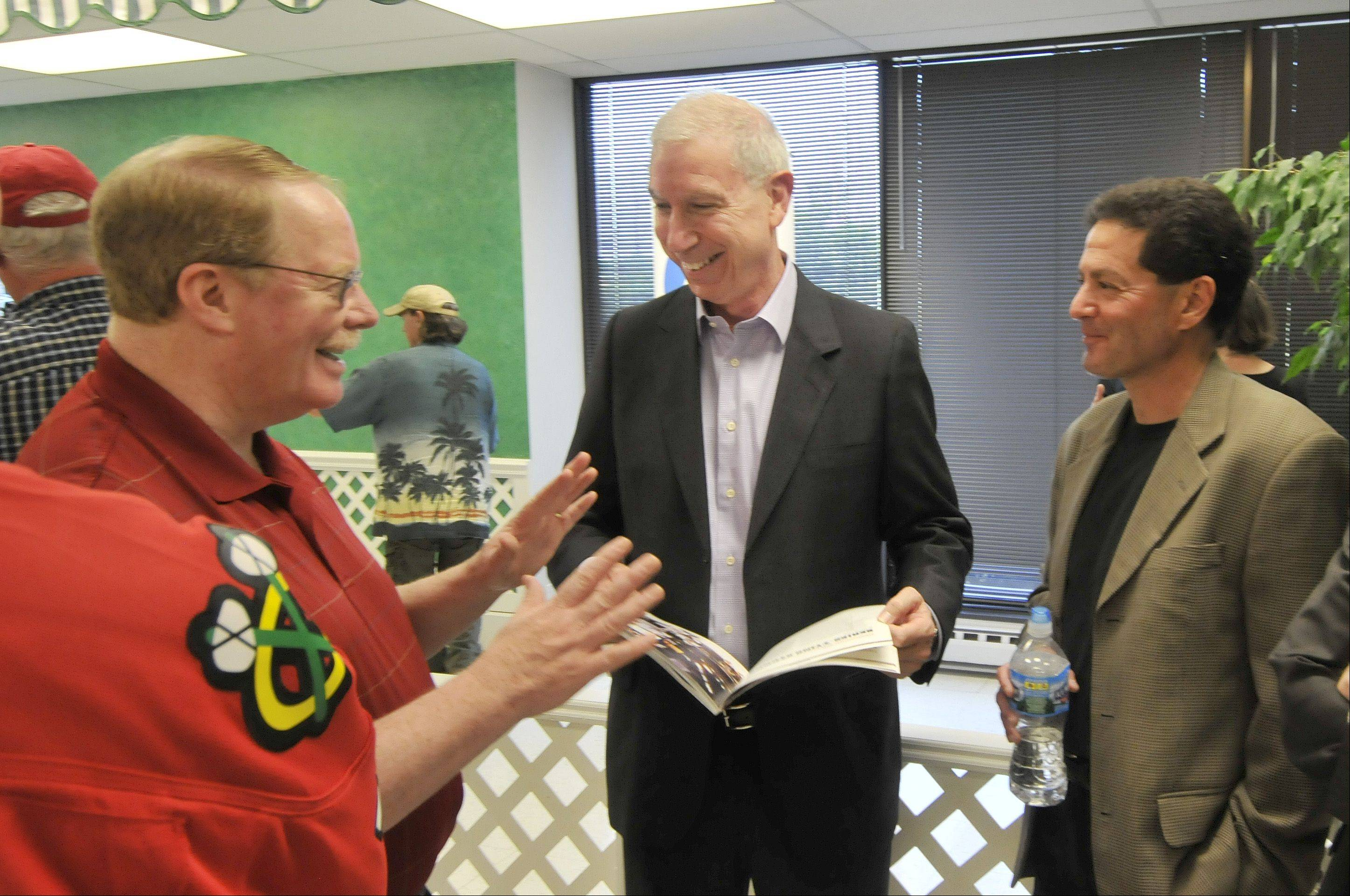 "The Stanley Cup made a stop on its post-victory travels at the Daily Herald office in Arlington Heights on Friday. From left, Daily Herald Sports Editor Tom Quinlan, Blackhawks President John F. McDonough, and Daily Herald sportswriter Barry Rozner look at the Herald's commemorative book ""Unstoppable"" which was presented to McDonough."