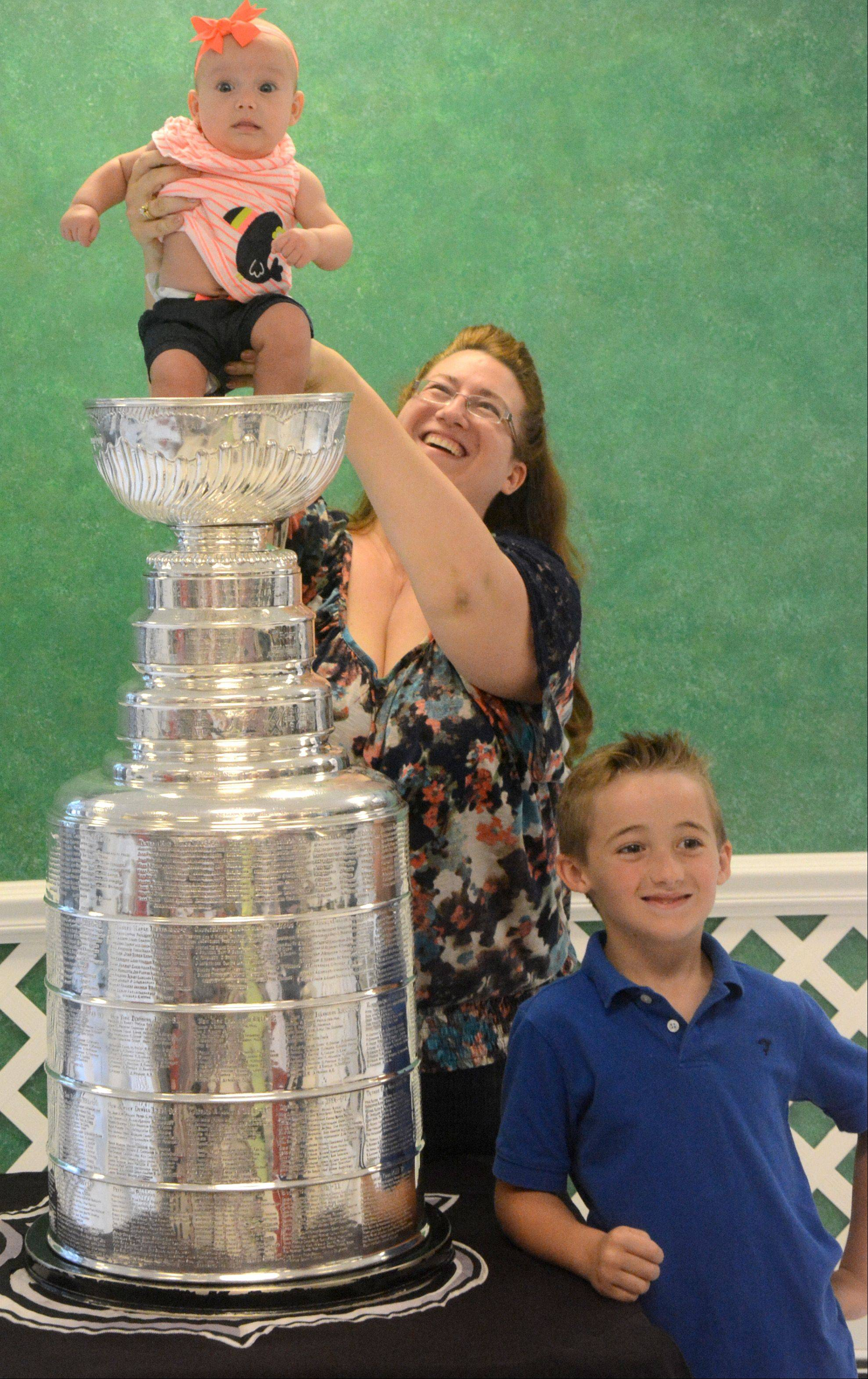 Candace Lewnard, of Mount Prospect, holds daughter Sofia, 1, in the Stanley Cup as brother Michale, 7, poses for a photo at the Daily Herald office Friday in Arlington Heights.
