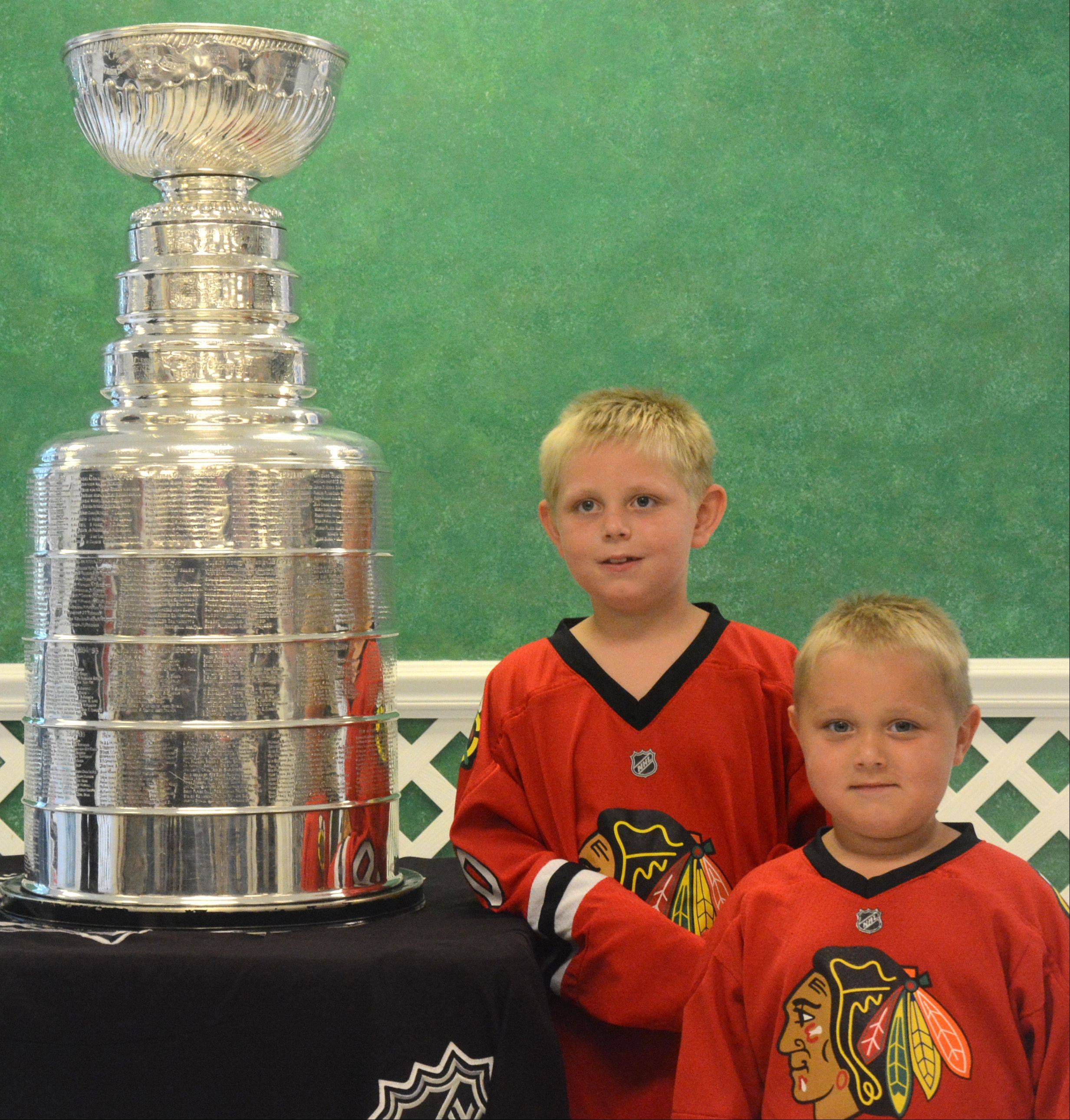 From left, Ryan Kowalski, 7, and Joshua Kowalski, 4, of Round Lake, take a picture with the Stanley Cup at the Daily Herald office Friday in Arlington Heights.
