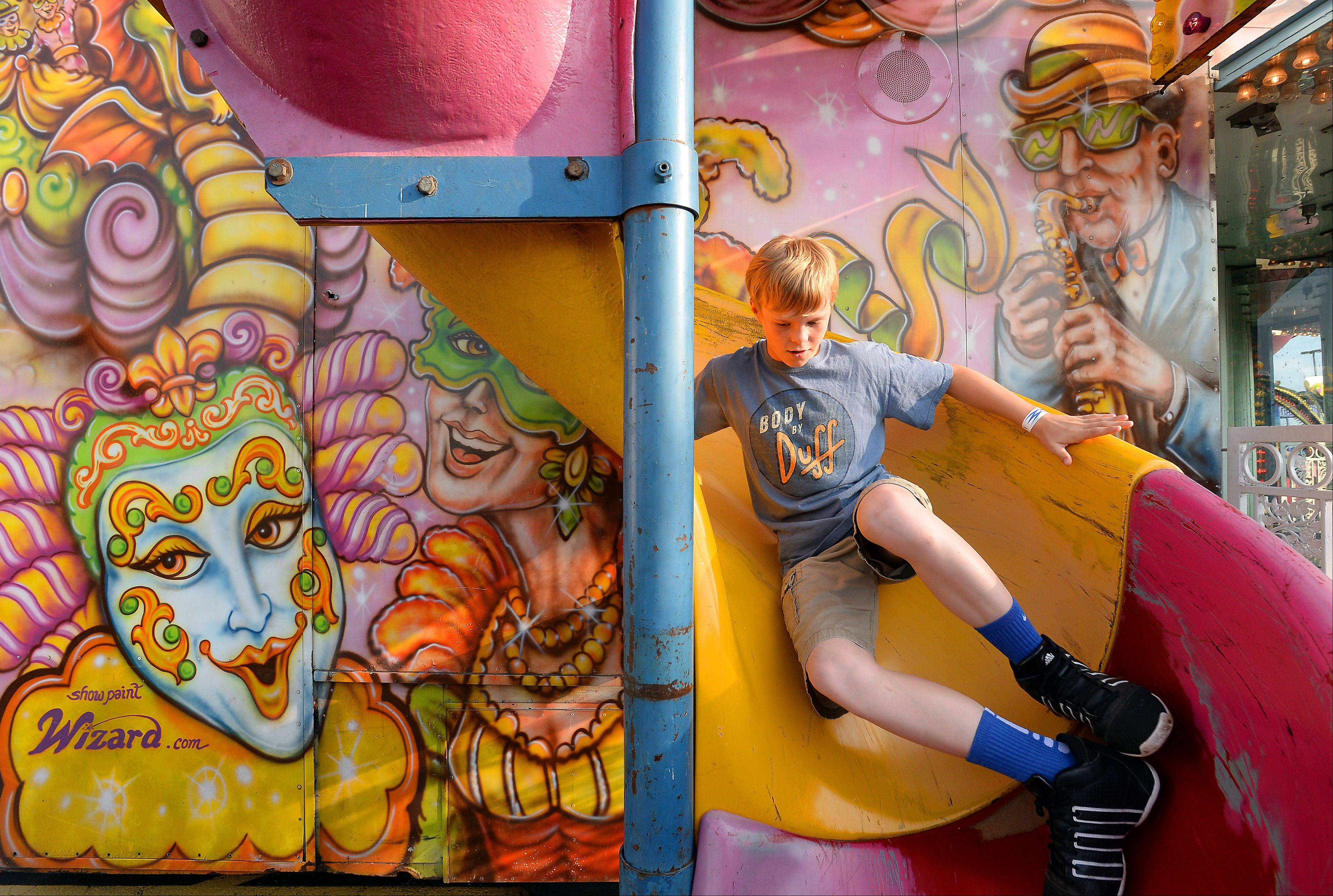 Jackson Reuter, 13, of Elgin takes a run on the Mardi Gras slide at the Northwest Fourth-Fest in Hoffman Estates on Friday.