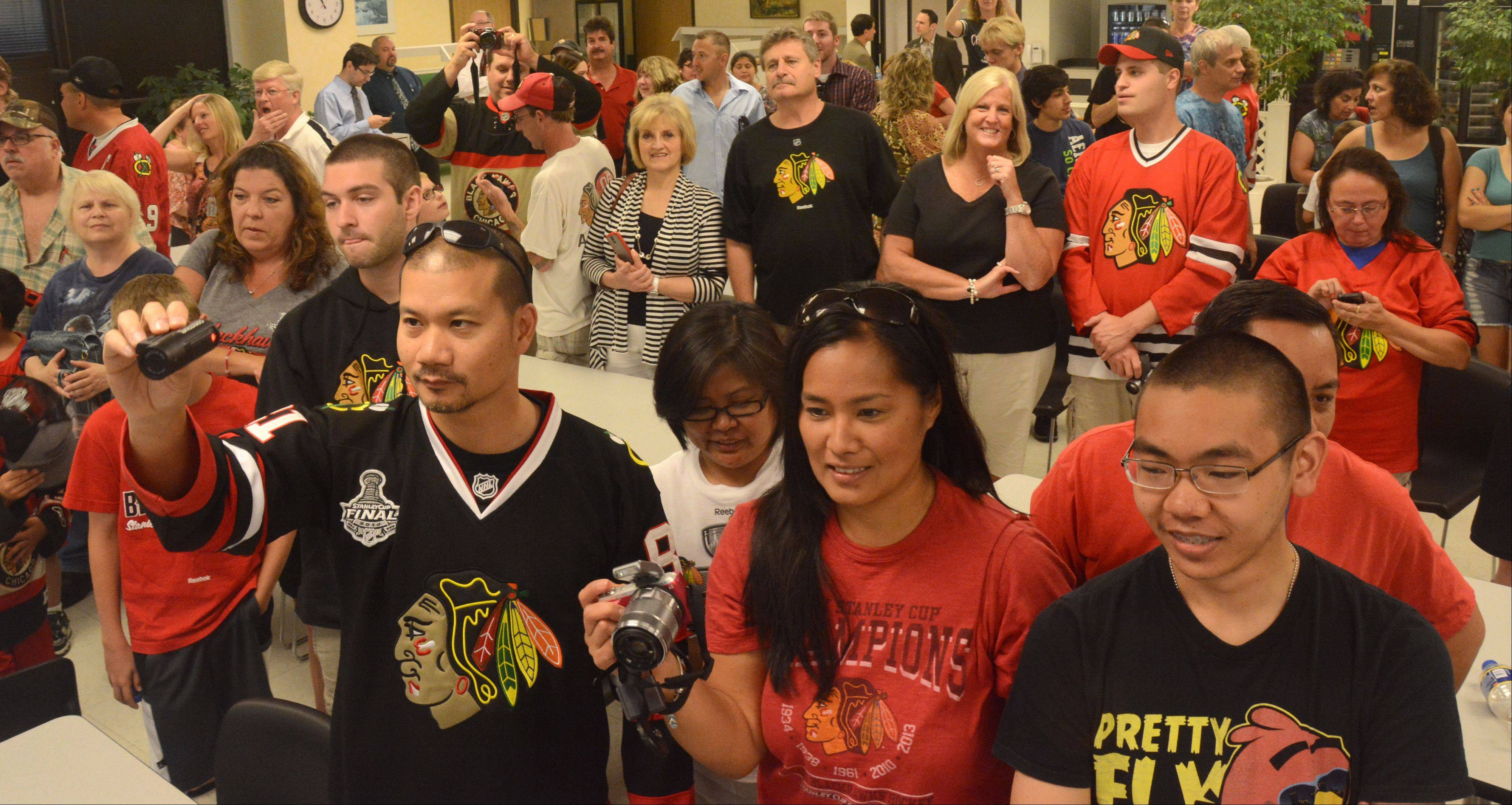 A line of people gathered for a photo opportunity with the Stanley Cup at the Daily Herald office Friday in Arlington Heights.