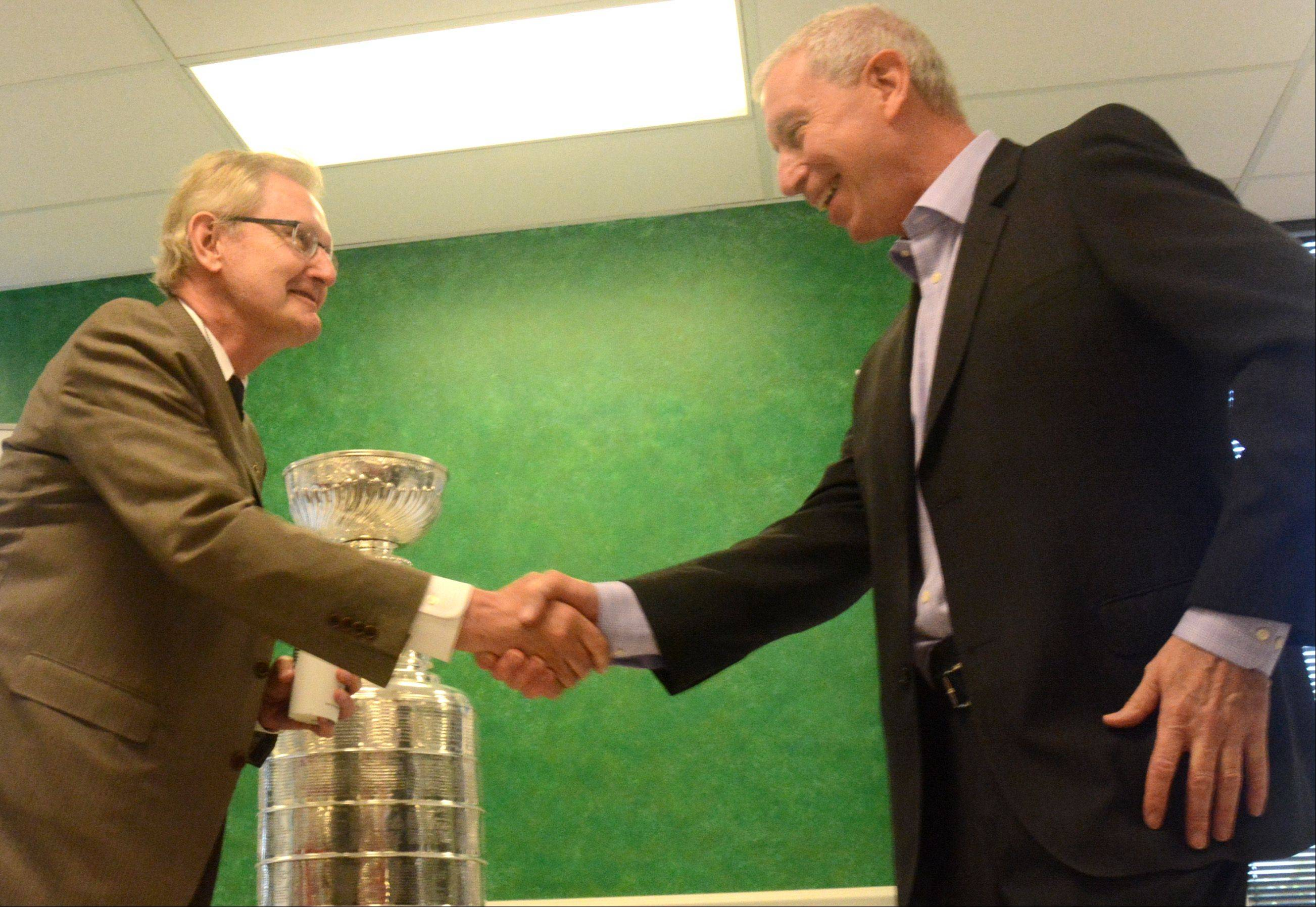 Hawks President John McDonough, left, shakes hands with Bob Paddock Jr. at the Daily Herald office Friday in Arlington Heights.