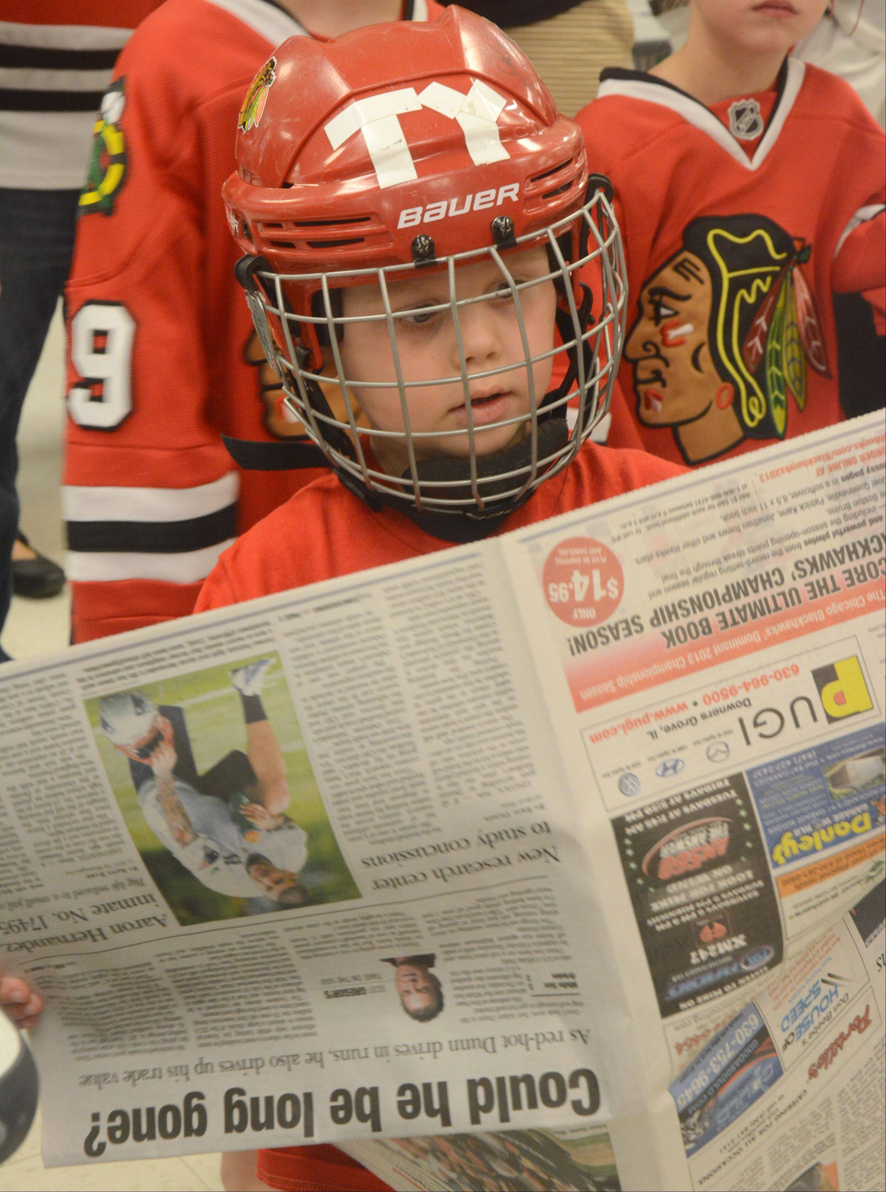 Tyler Seiwert, 4, of Park Ridge, catches up with the sports section while waiting for his turn with the Stanley Cup at the Daily Herald office Friday in Arlington Heights.