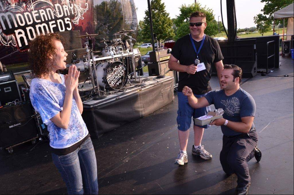 Steve Kemper, 23, of Streamwood, proposes to Michaela Neu, 27, his girlfriend of two years, at the Northwest Fourth-Fest in Hoffman Estates Thursday.
