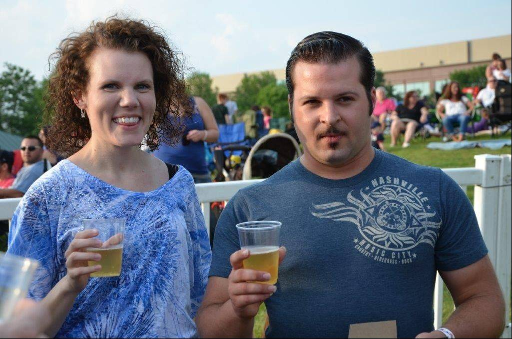 Steve Kemper, 23, of Streamwood, and Michaela Neu, 27, his girlfriend of two years, make a toast at the Northwest Fourth-Fest in Hoffman Estates after their onstage engagement Thursday.