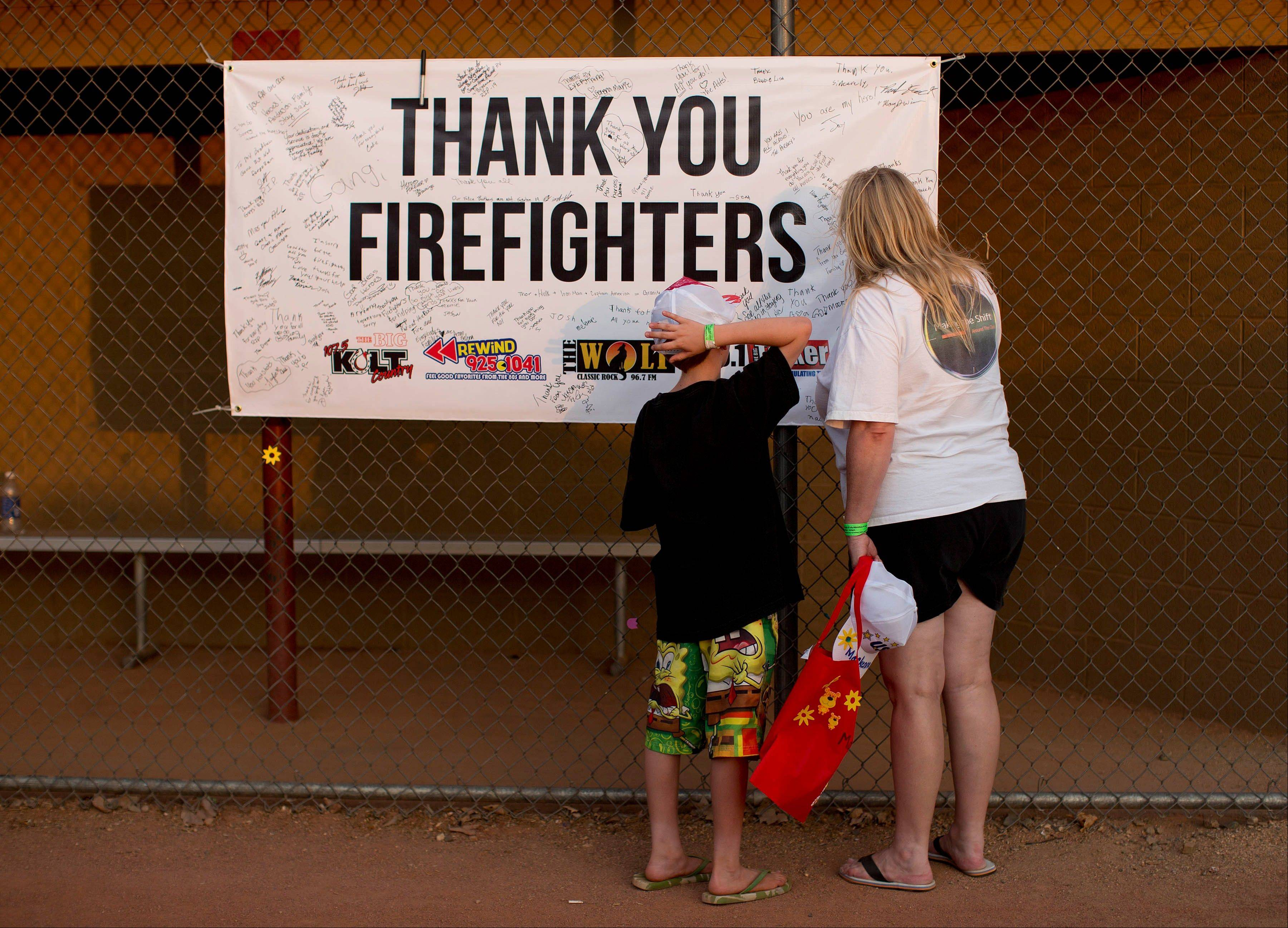 Ten-year-old Lyam Davis, left, watches as his mother, Rachel Davis, both of Phoenix, Ariz., sign a banner during the Fourth of July celebration at Pioneer Park, Thursday, July 4, 2013 in Prescott, Ariz. in honor of the 19 fallen Granite Mountain Hotshot firefighters who died fighting a blaze near Yarnell, Ariz. on Sunday.