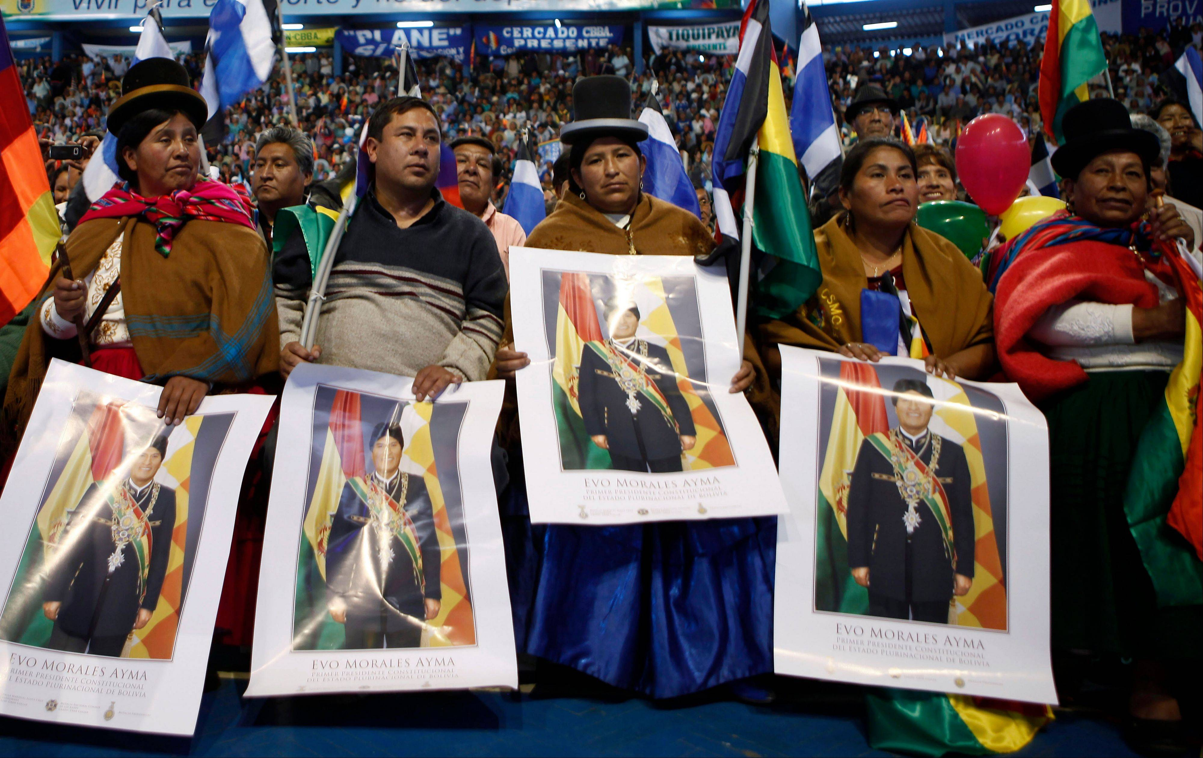 Aymara women hold a posters of Bolivia's President Evo Morales during a welcome ceremony for presidents attending an extraordinary meeting in Cochabamba, Bolivia, Thursday, July 4, 2013. Leaders of Uruguay, Ecuador, Suriname, Argentina and Venezuela are meeting in Bolivia Thursday in support of Morales, who said Thursday that the rerouting of his plane in Europe, over suspicions that National Security Agency leaker Edward Snowden was on board was a plot by the U.S. to intimidate him and other Latin American leaders.