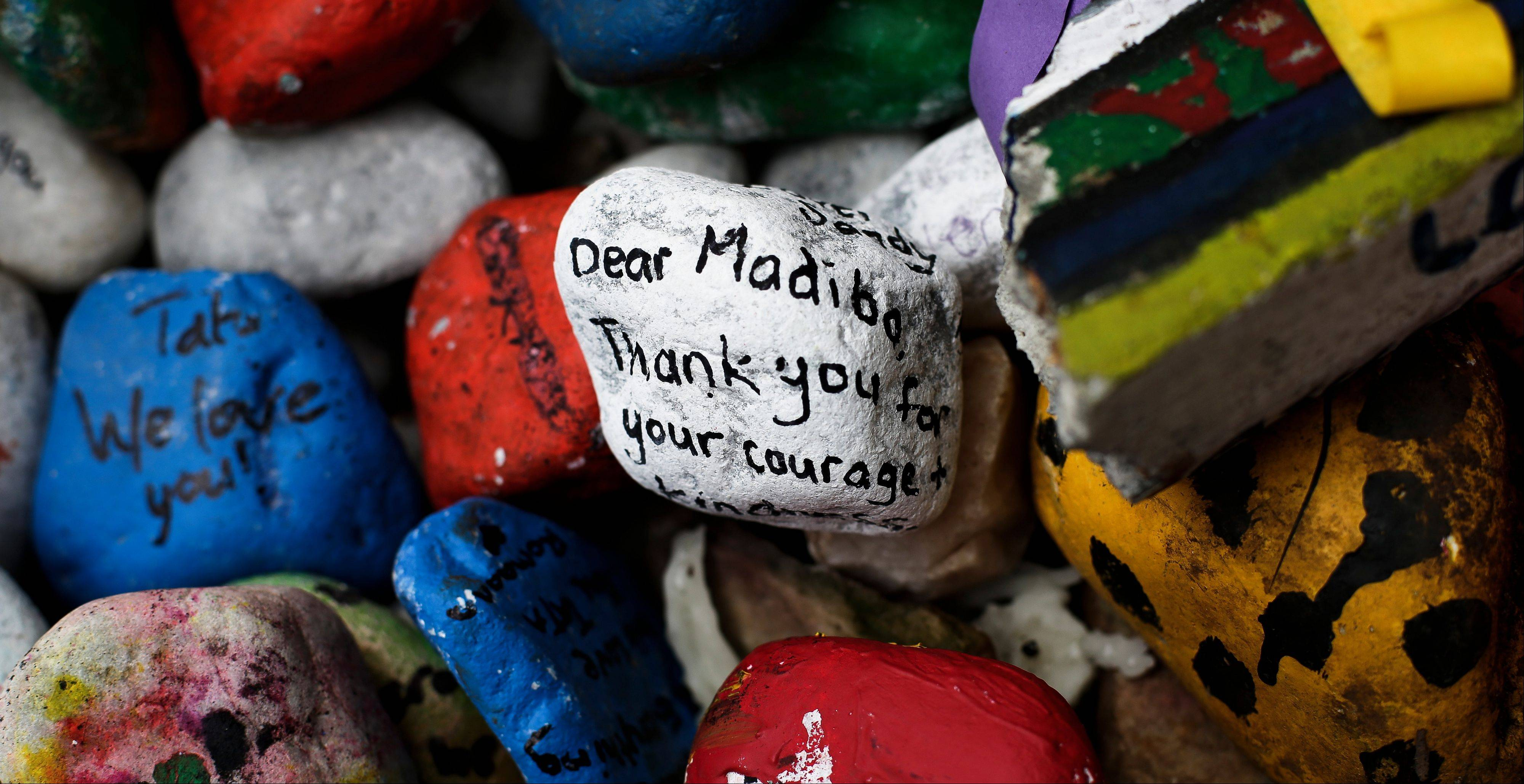 "Stones with well wishes in support of former South African President Nelson Mandela lay in front of his house in Johannesburg, South Africa, Friday, July 5, 2013. Mandela, who was hospitalized on June 8, remains in critical but stable condition according to the office of President Jacob Zuma, who visited the anti-apartheid leader on Thursday, and the president's office also said doctors denied reports that 94-year-old Mandela is in a ""vegetative state."""
