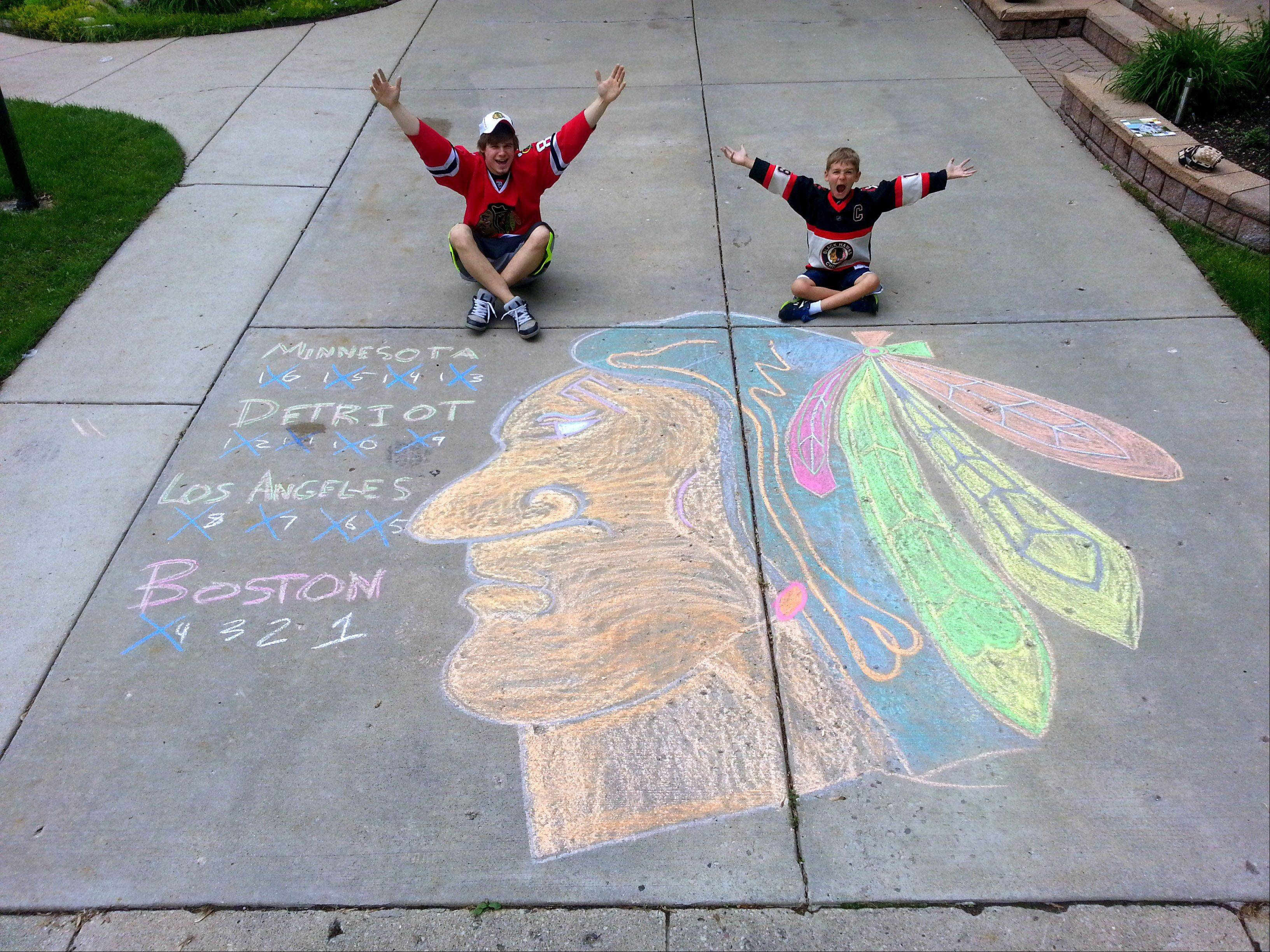 Daniel and Sebastian Dorszewski mark their Blackhawks spirit with a chalk drawing on a Palatine driveway of the Chicago Blackhawks logo.