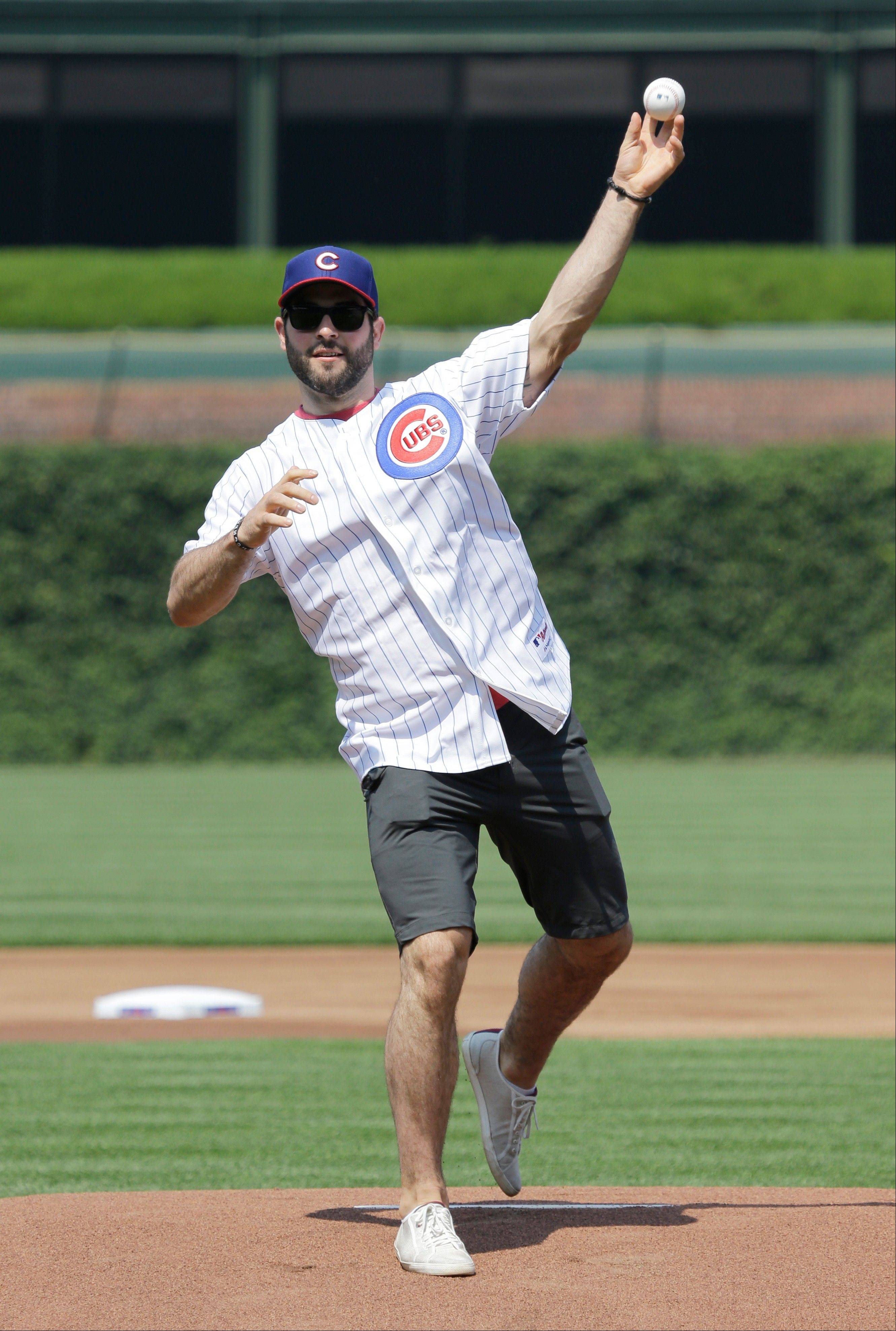 The Blackhawks' Brandon Bollig throws a ceremonial first pitch before Friday's game between the Pirates and Cubs at Wrigley Field.