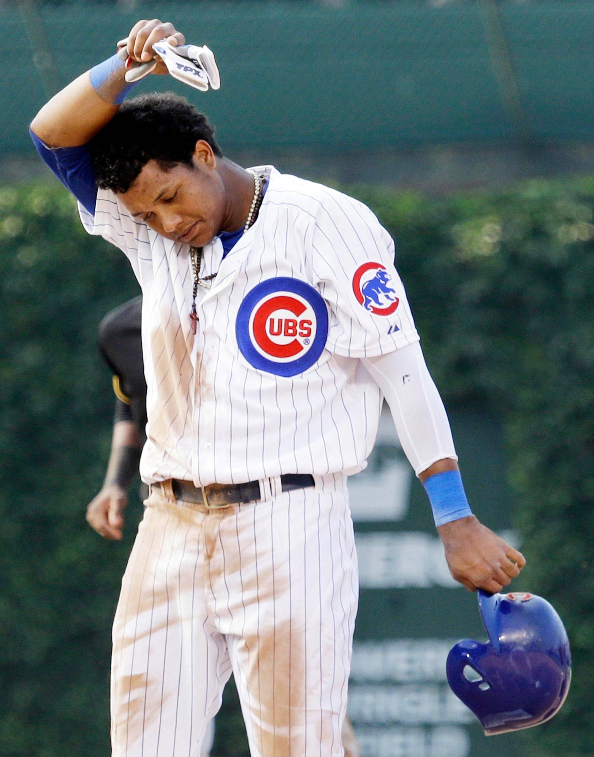 The Cubs' Starlin Castro wipes his face after he was tagged out by Pittsburgh Pirates second baseman Neil Walker during the eighth inning Friday in Chicago