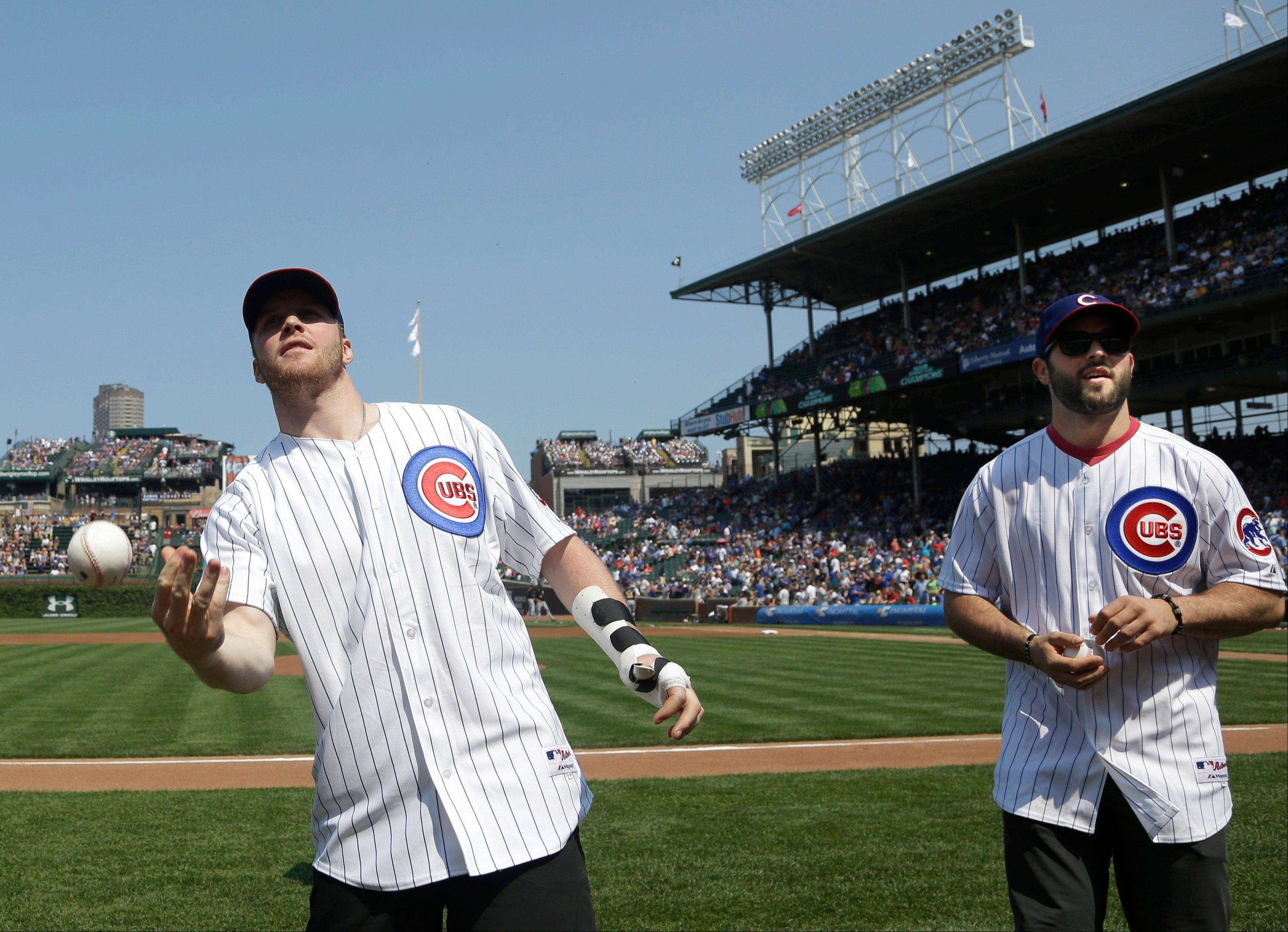 Bryan Bickell, left, throws a ball to fan as fellow Blackhawk Brandon Bollig watches before Friday's game between the Pittsburgh Pirates and the Chicago Cubs at Wrigley Field