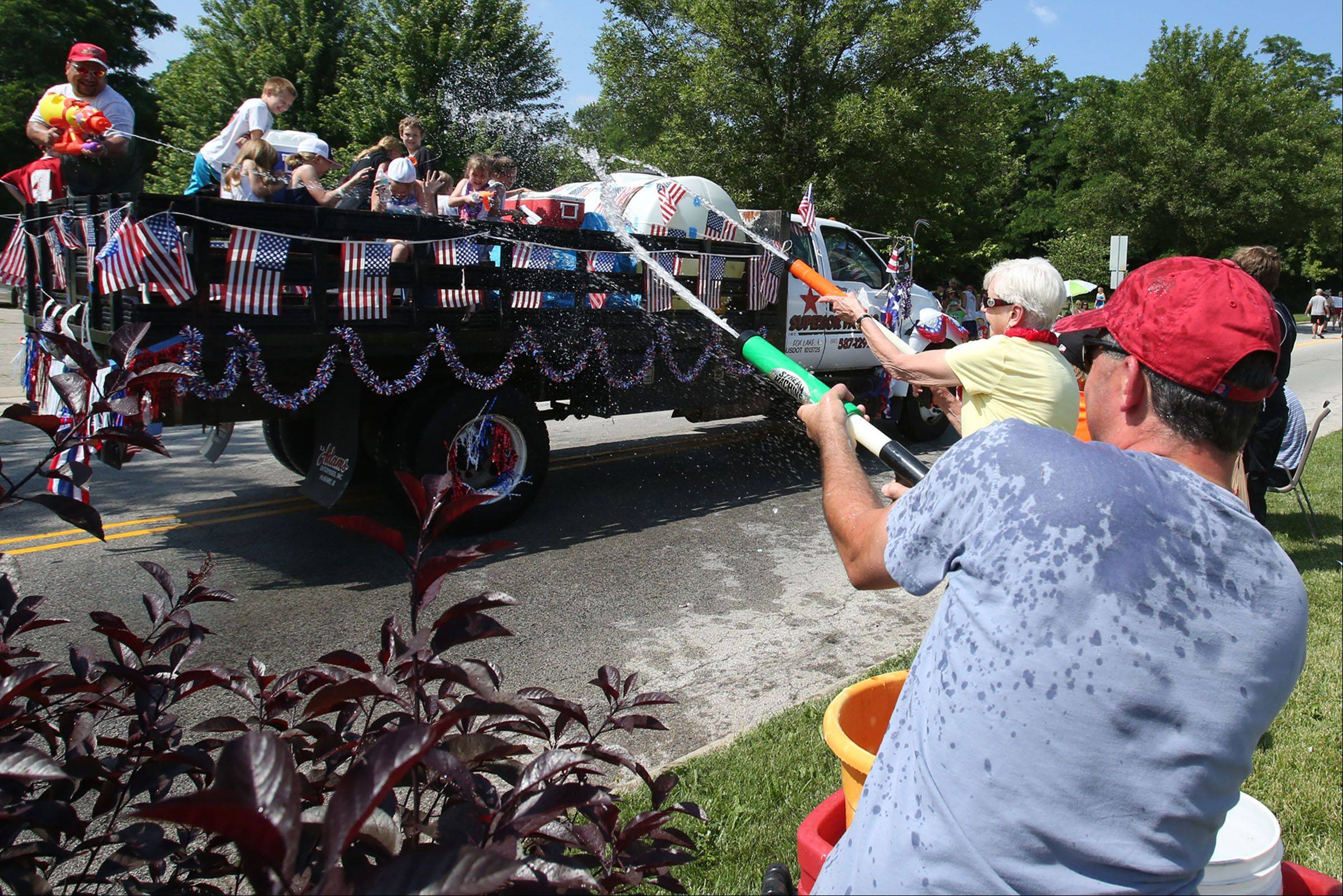 James Vass and his mom, Angie, both of Fox Lake, use water cannons Saturday to sneak-attack floats that travel past their spot along the Celebrate Fox Lake parade on Grand Avenue after starting at Grant High School.