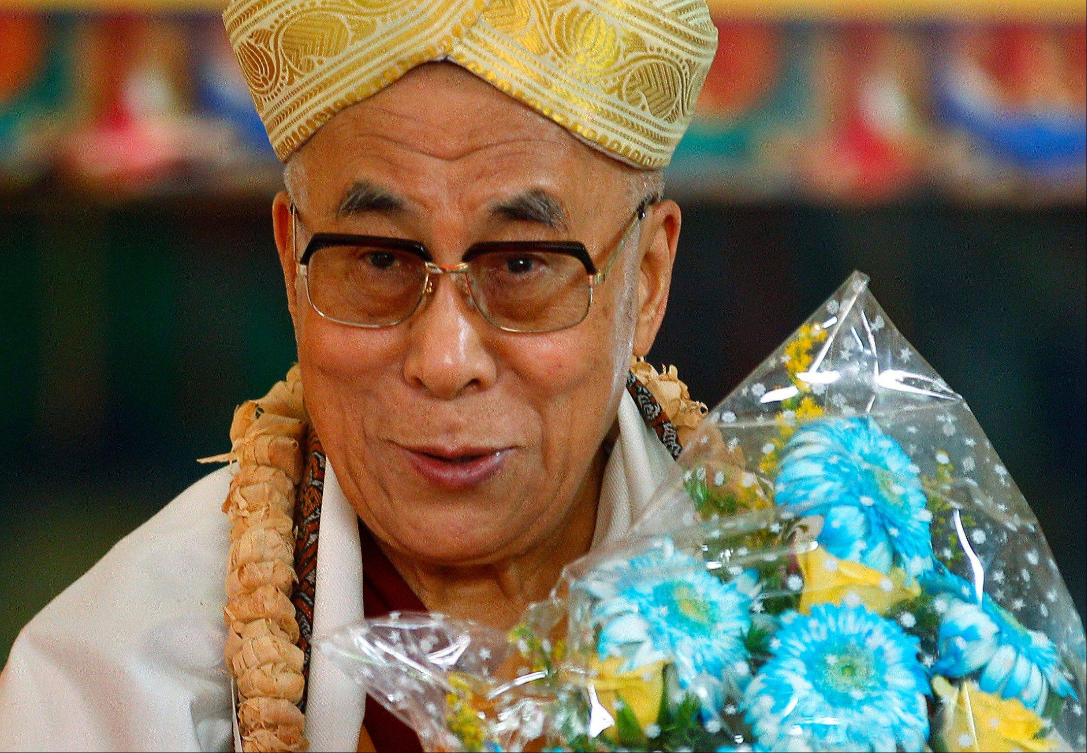 "Tibetan spiritual leader the Dalai Lama reacts after he was presented a headgear and a bouquet of flowers during an event organized to celebrate his 78th birthday at a Tibetan Buddhist monastery in Bylakuppe, about 137 miles southwest of Bangalore, India, Saturday, July 6. Speaking after an interfaith meeting, he said 150,000 Tibetans living abroad represent ""six million Tibetans (in China) who have no freedom or opportunity to express what they feel."""