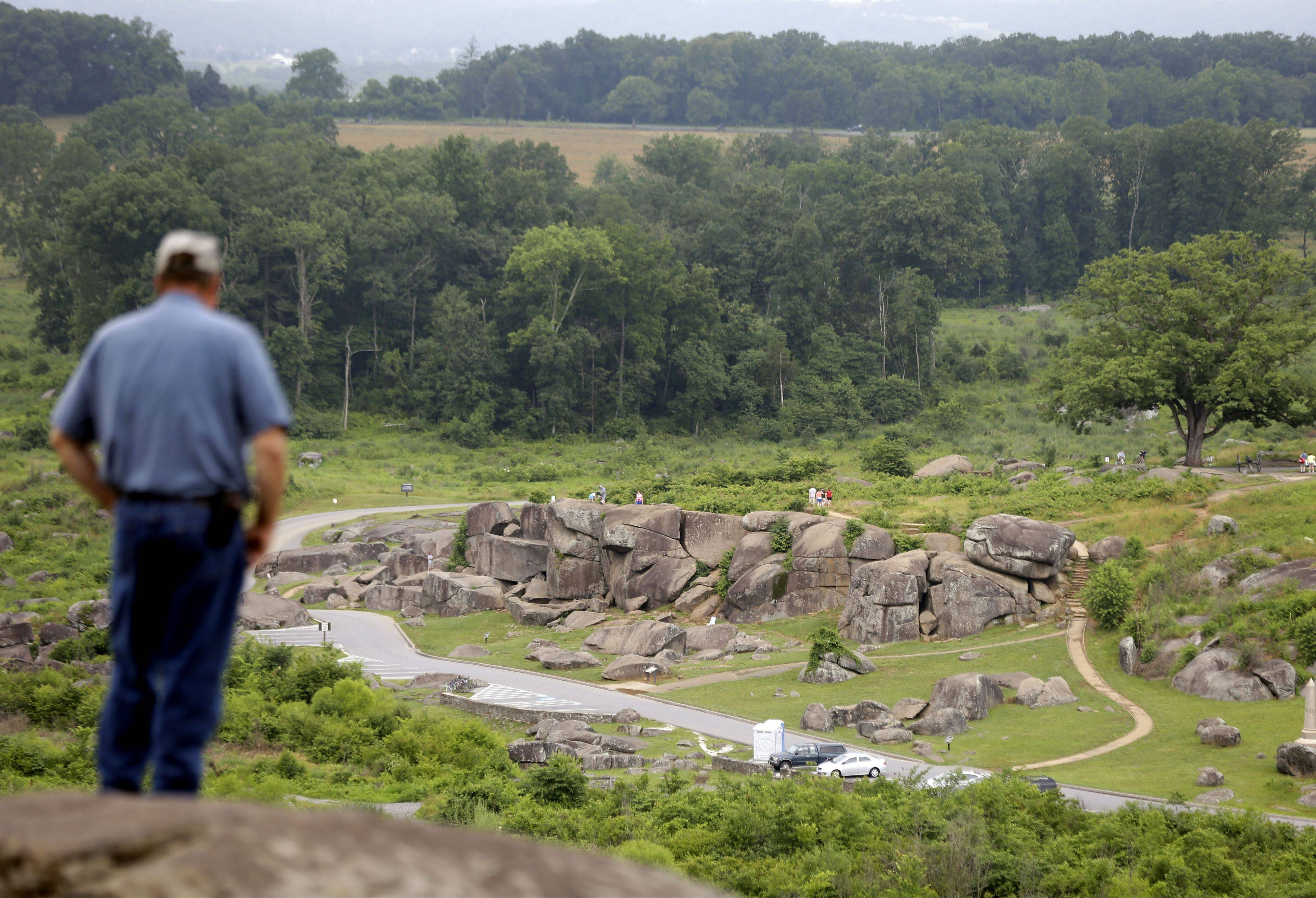 Tim Jenkins of Virginia views the Devil's Den from Little Round Top during ongoing activities commemorating the 150th anniversary of the Battle of Gettysburg.