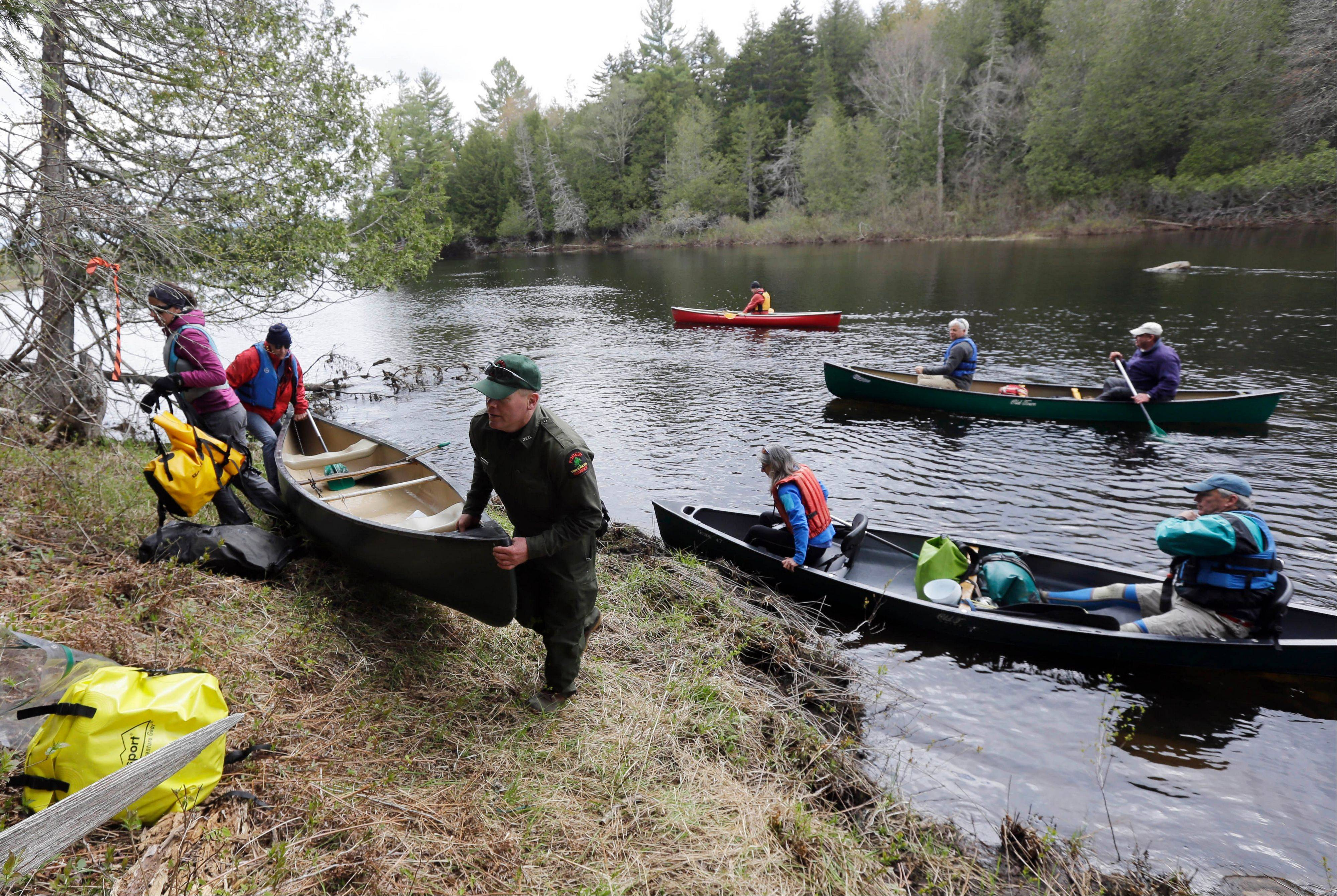 State Forest Ranger Delbert Jeffery, center, helps canoeists with their canoes before a portage during a trip on the upper Hudson River in Newcomb, N.Y.