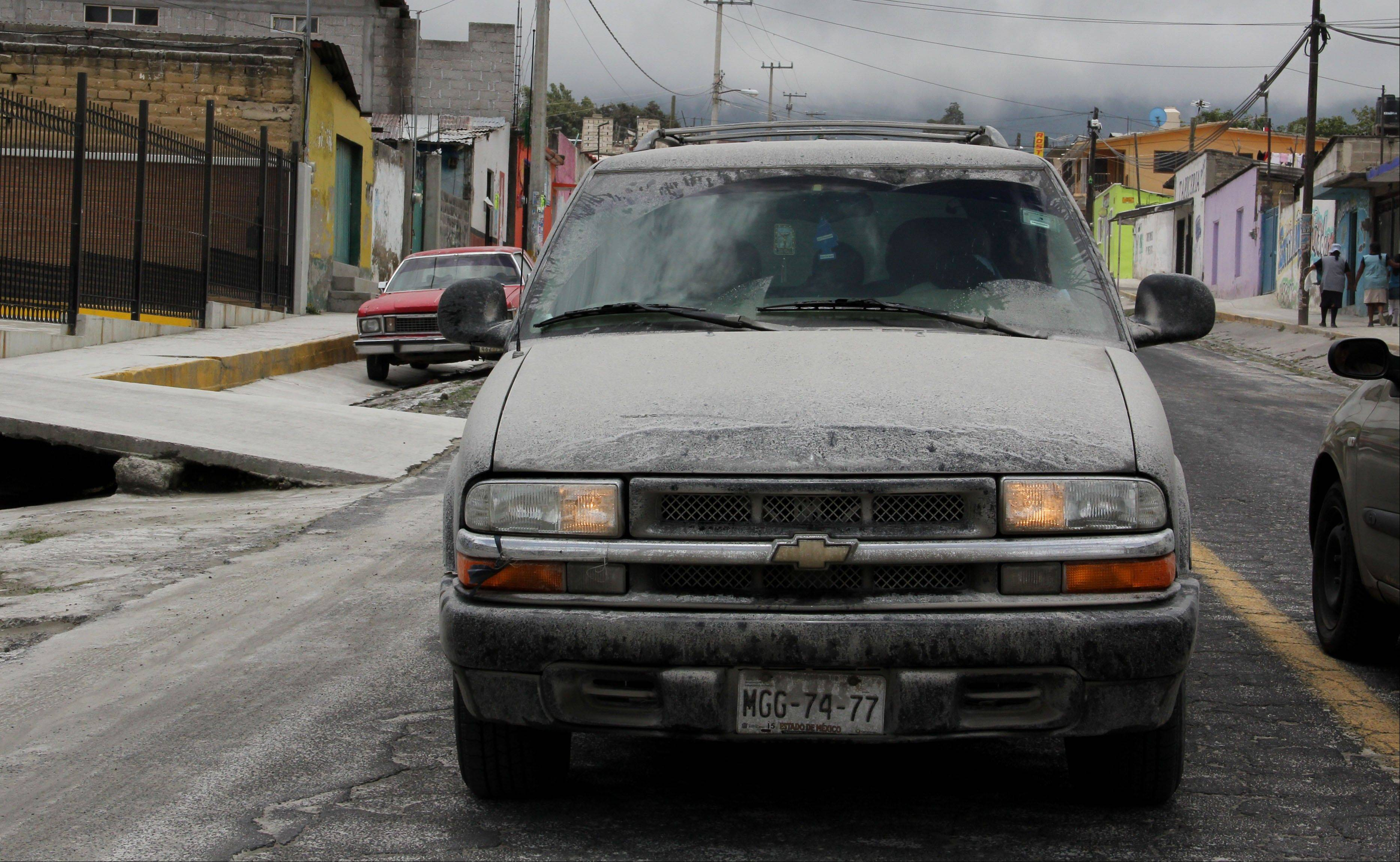Volcanic ash coats the streets and a vehicle in San Pedro Nexapa, Mexico, Saturday. Just east of Mexico City, the Popocatepetl volcano has spit out a cloud of ash and vapor 2 miles (3 kilometers) high over several days of eruptions.